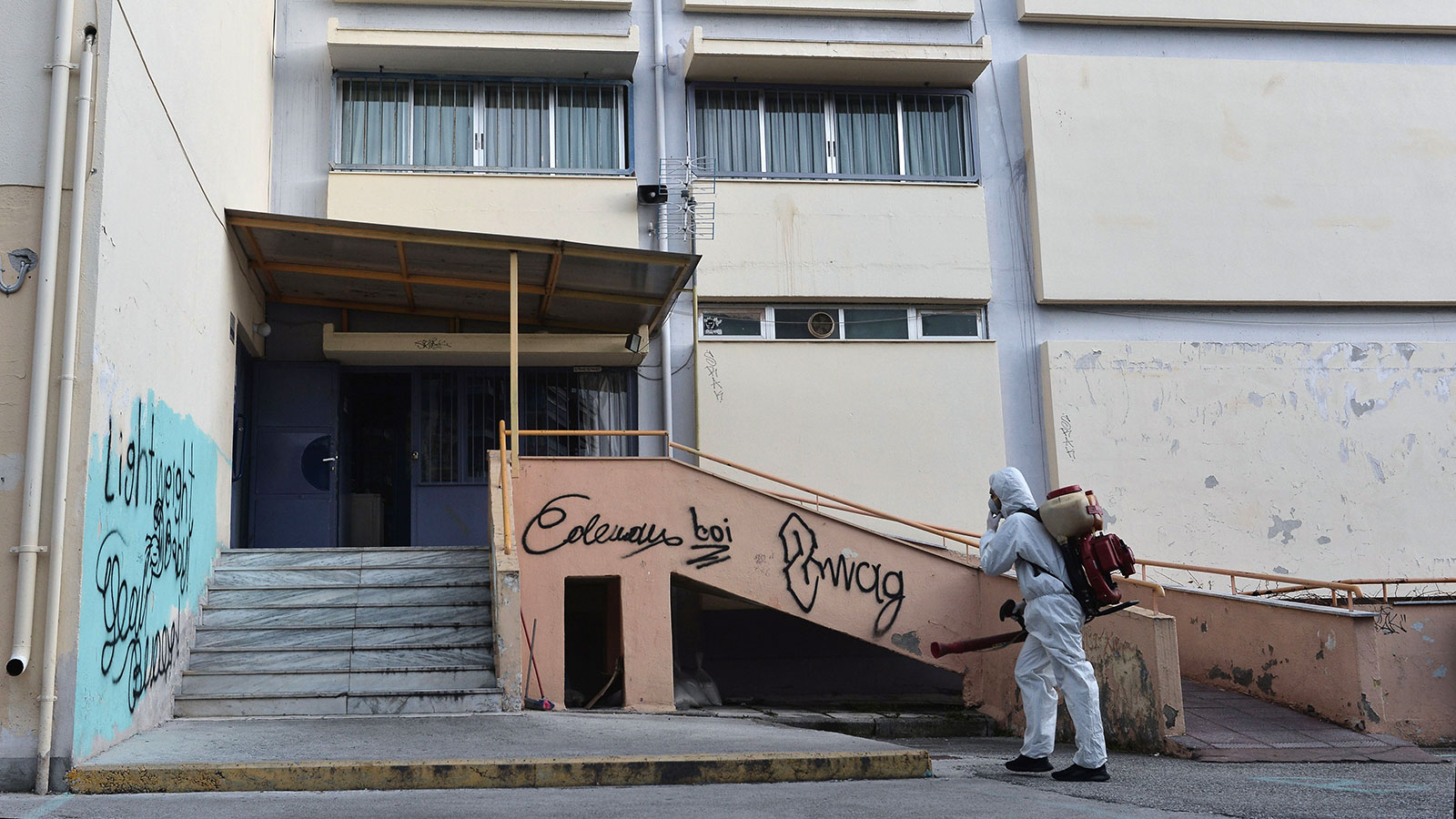 A worker sprays disinfectant as part of preventive measures against the spread of the COVID-19, the novel coronavirus, in a school in Thessaloniki, Greece on February 27.