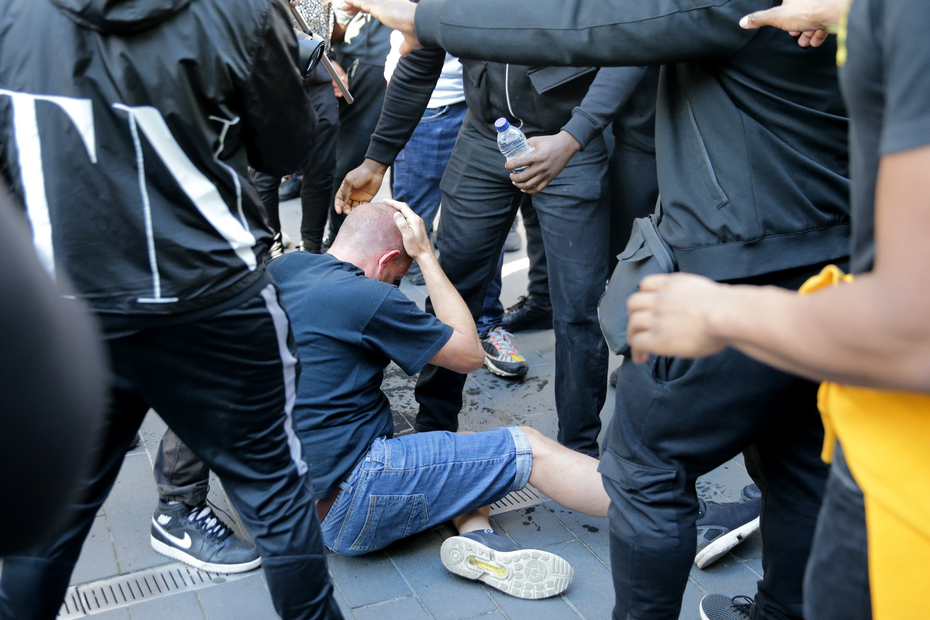 A man rubs his head as he sits on the ground after a group of men carried him away after he was allegedly attacked by some of the crowd of protesters on the Southbank near Waterloo station in London on June 13, 2020.