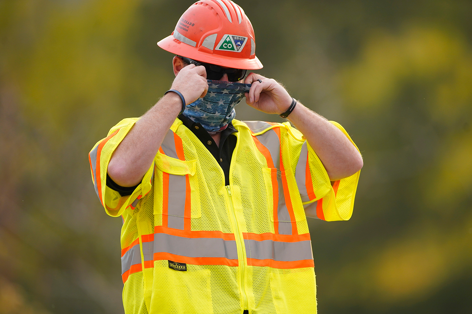 A Colorado Department of Transportation worker pulls on his face covering while staffing a roadblock into a housing area along Highway 7 as several wildfires burn in the state on October 21, in Lyons, Colorado.