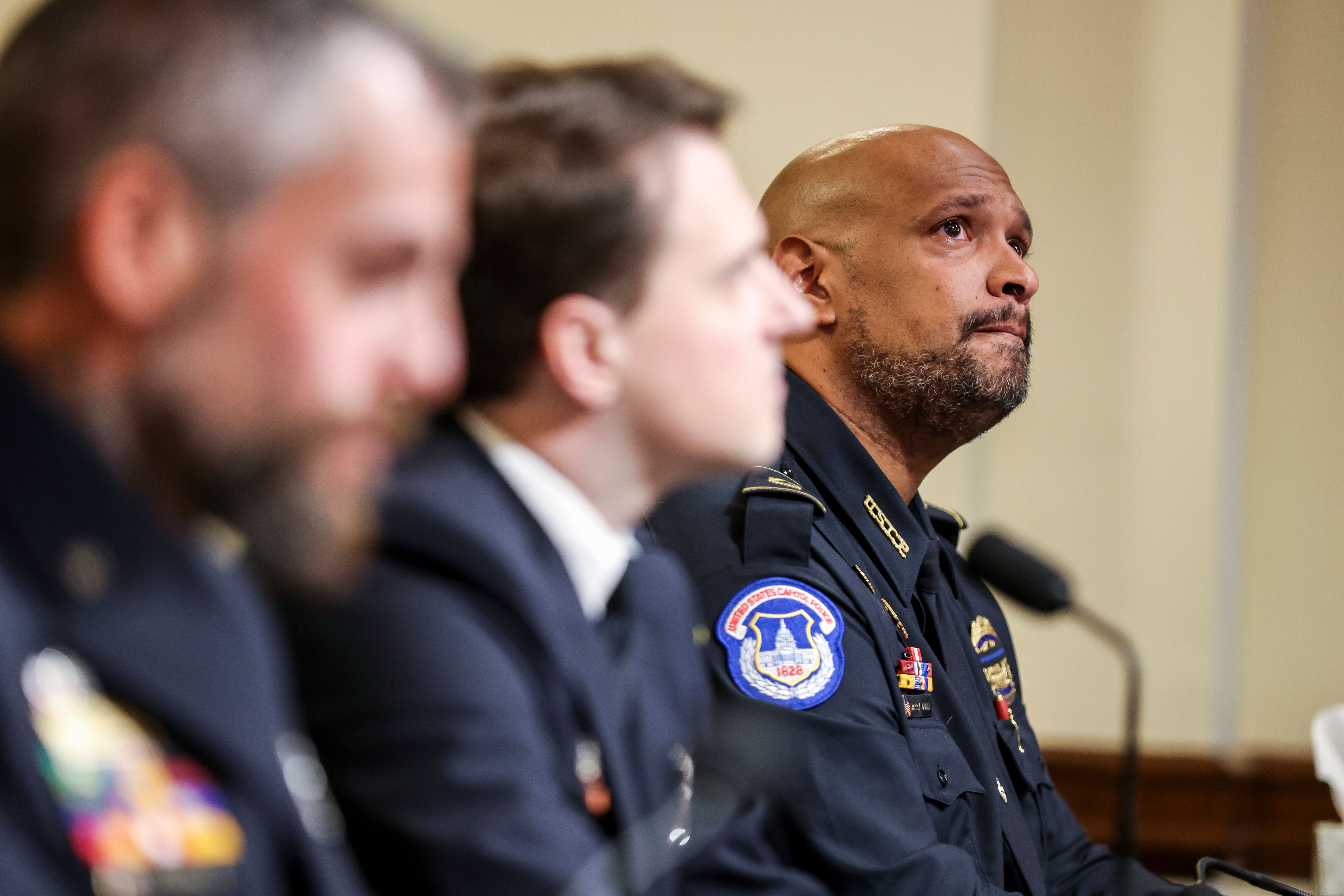 Capitol Police Officer Harry Dunn, at right, watches a video during the House select committee hearing on the January 6 attack on Capitol Hill on Tuesday, July 27.