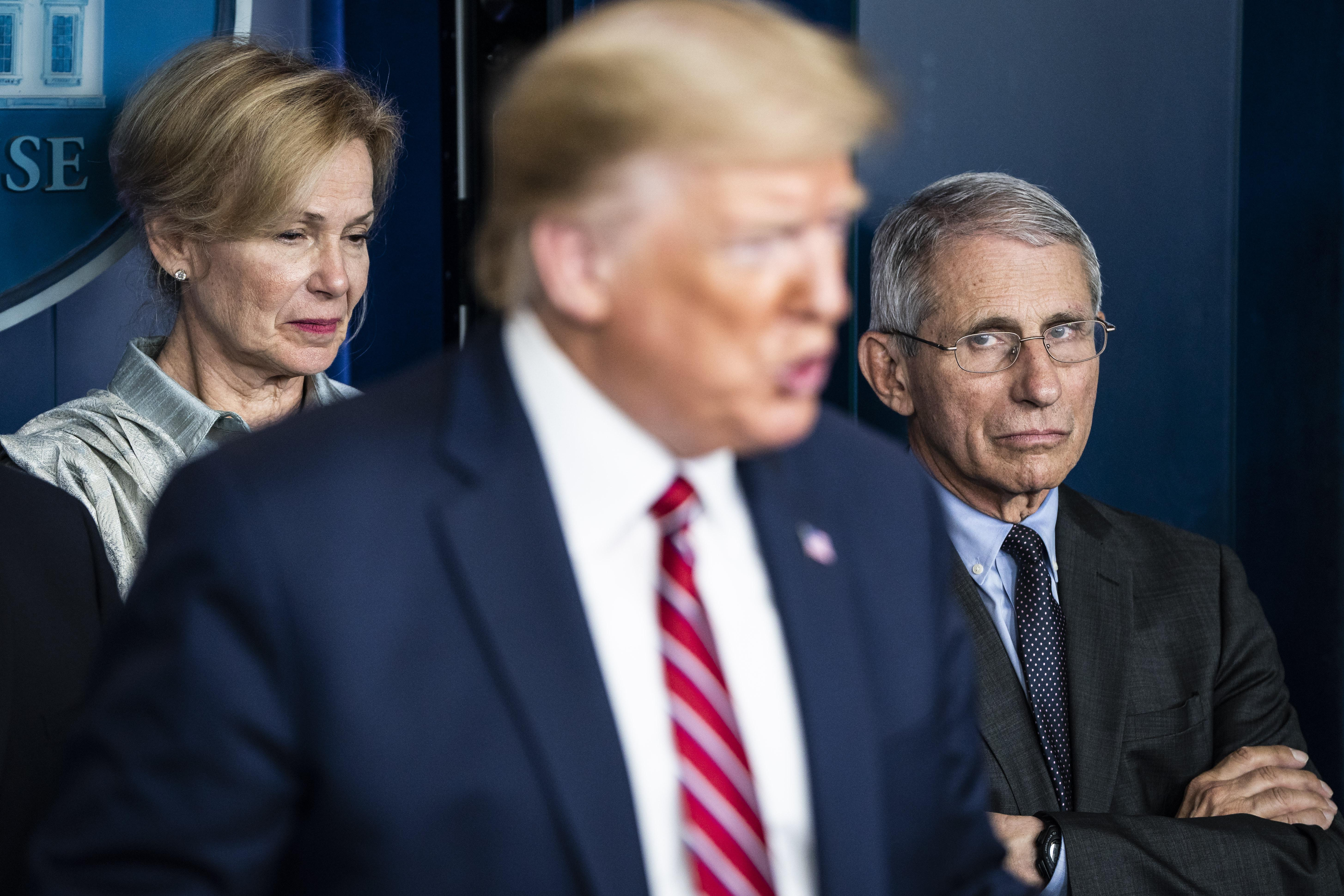 From left in background, Dr. Deborah Birx and Dr. Anthony Fauci listen as President Donald Trump speaks at a coronavirus briefing in Washington, DC, on March 20.