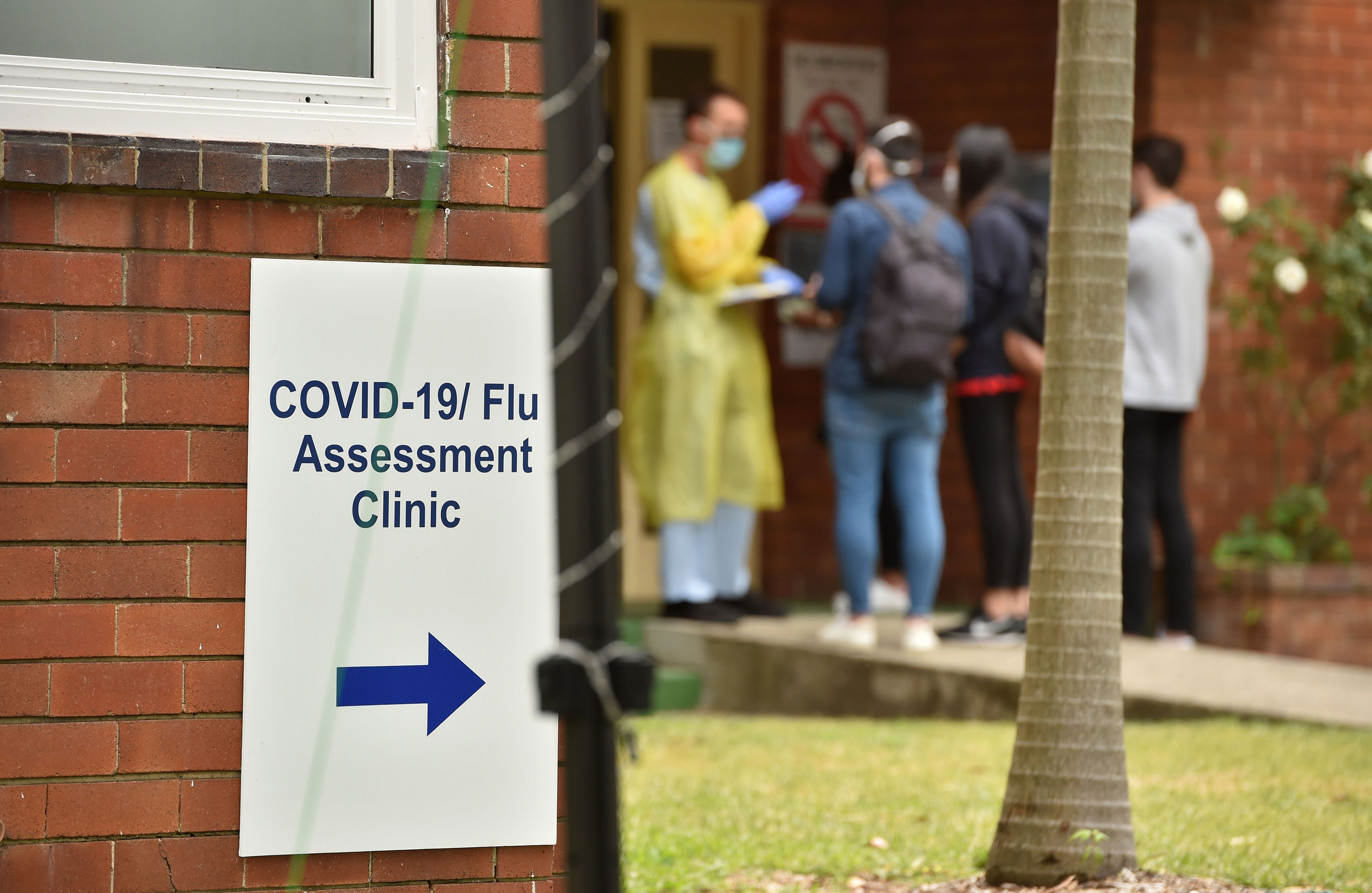 A health worker assists visitors at a Covid-19 testing center in Sydney on March 23.