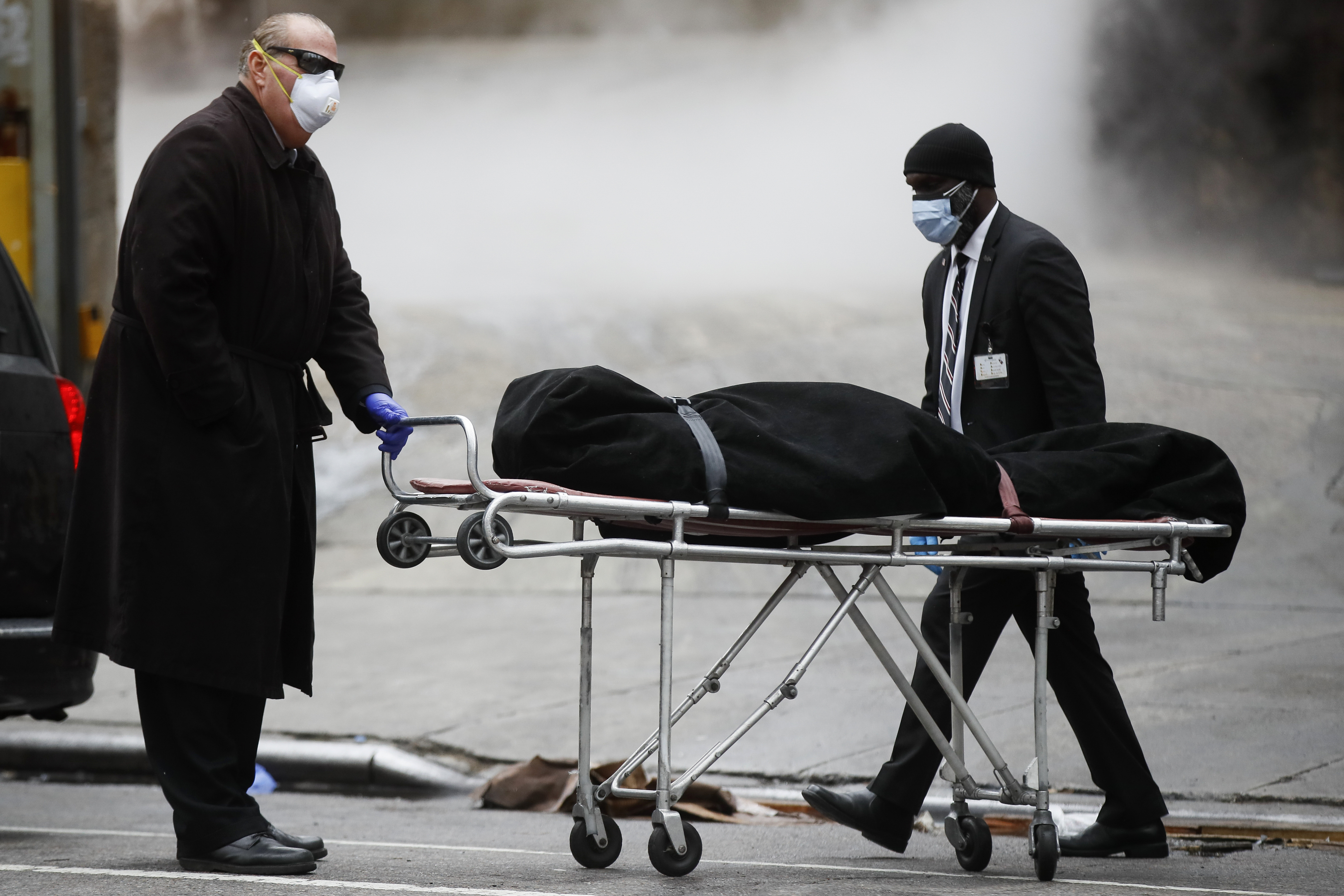 A funeral director wheels a body outside The Brooklyn Hospital Center in Brooklyn, New York, on April 9.