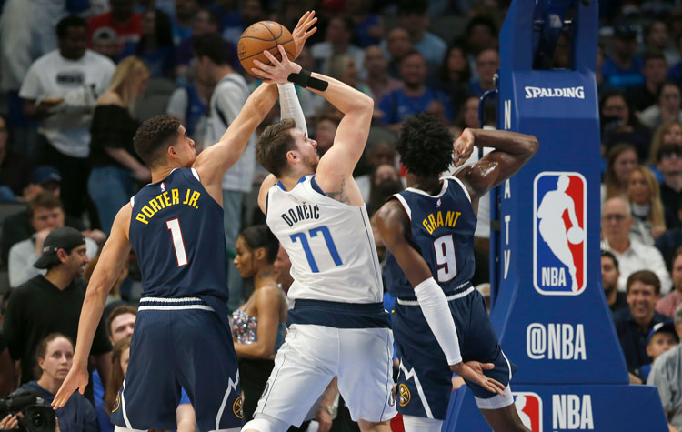 Dallas Mavericks guard Luka Doncic (77) shoots as Denver Nuggets forwards Michael Porter Jr. (1) and Jerami Grant (9) defend during the first half of an NBA basketball game Wednesday, March 11 in Dallas.