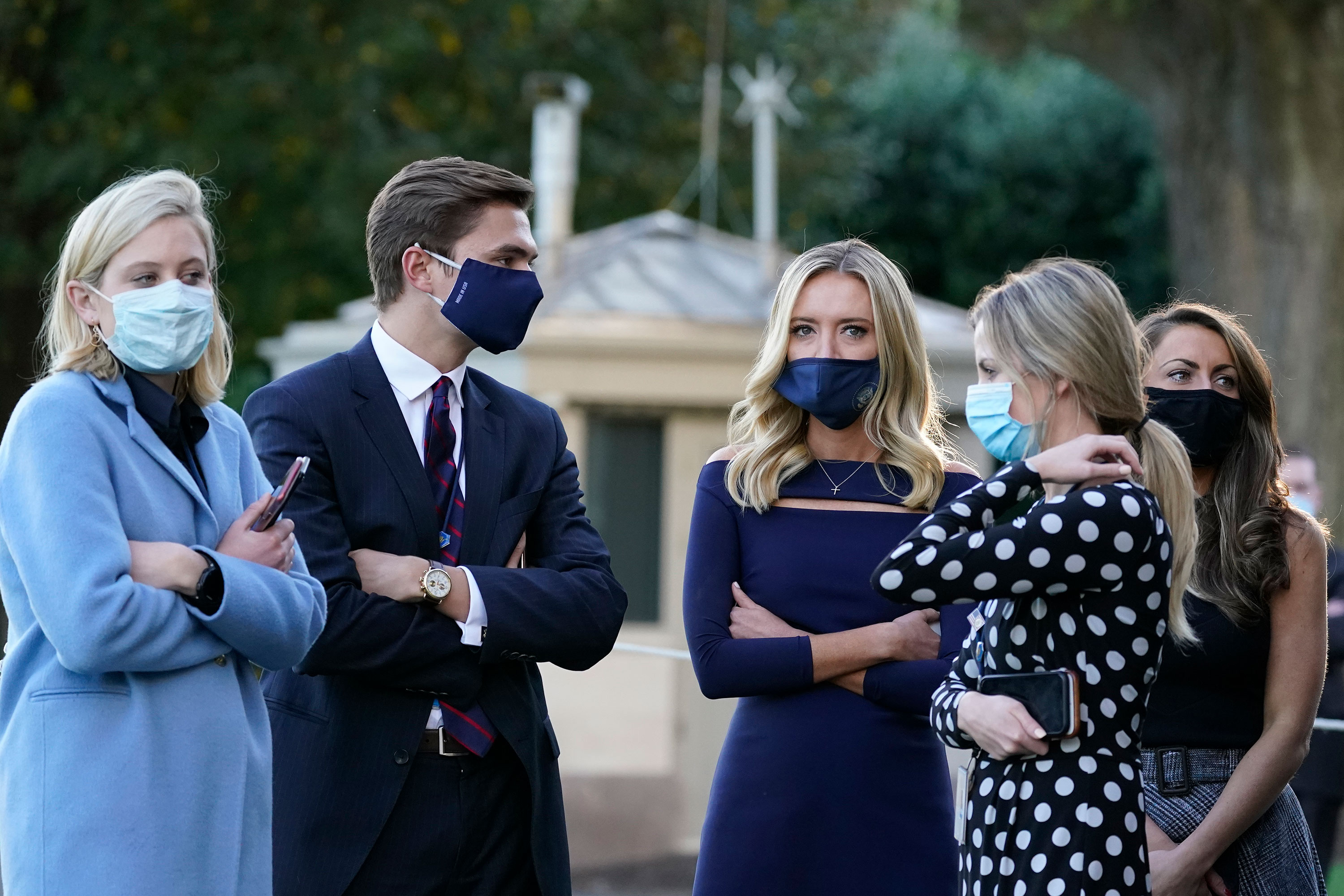 White House press secretary Kayleigh McEnany, third from left, waits with others as President Donald Trump prepares to leave the White House to go to Walter Reed National Military Medical Center on October 2 in Washington, DC.