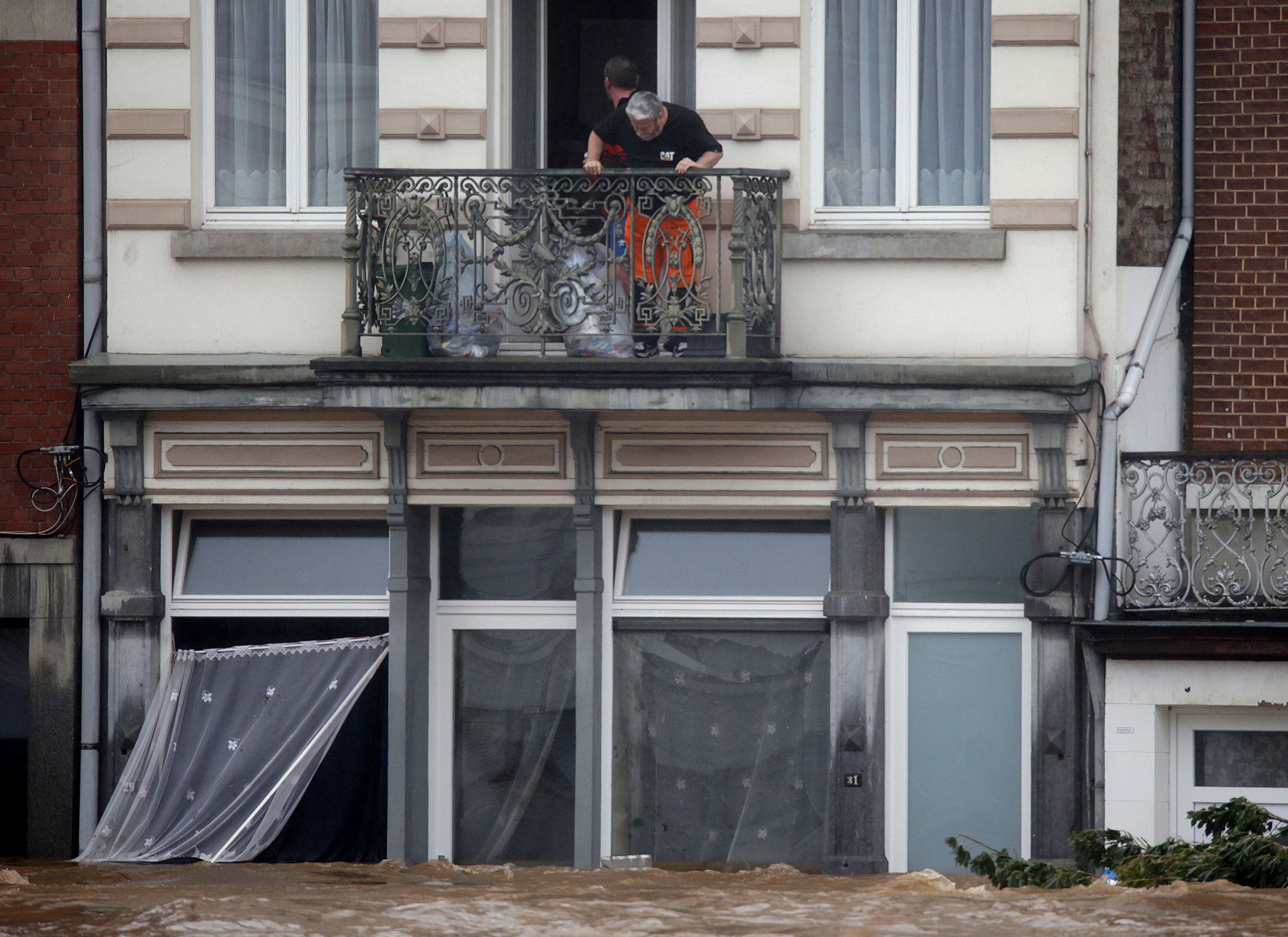 Rescue workers look down from a balcony as floodwaters run down a main street in Pepinster, Belgium, on Thursday.