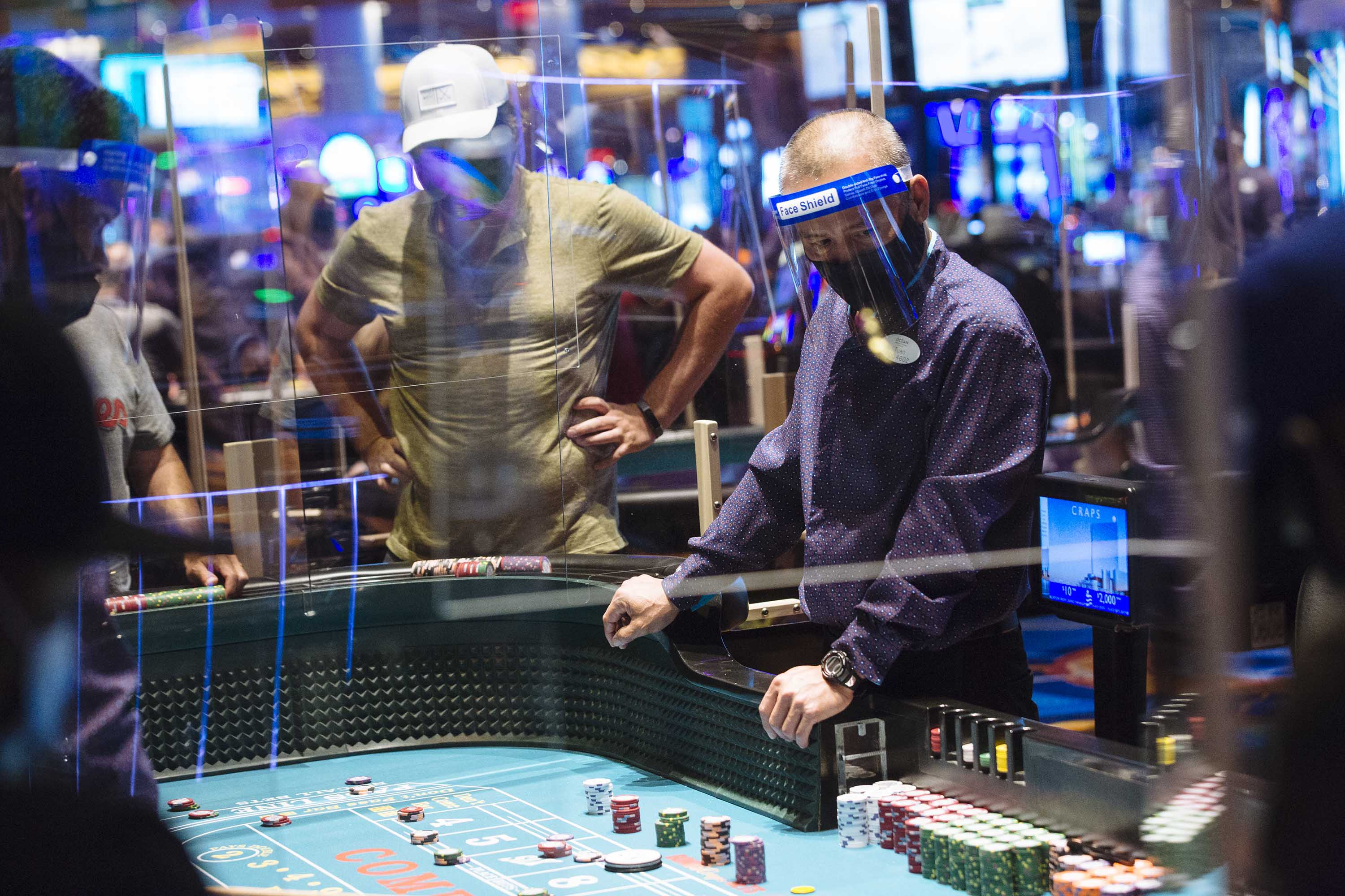 An employee wears a protective mask and face shield while overseeing the craps table at the Ocean Casino Resort in Atlantic City, New Jersey, in July 2020.
