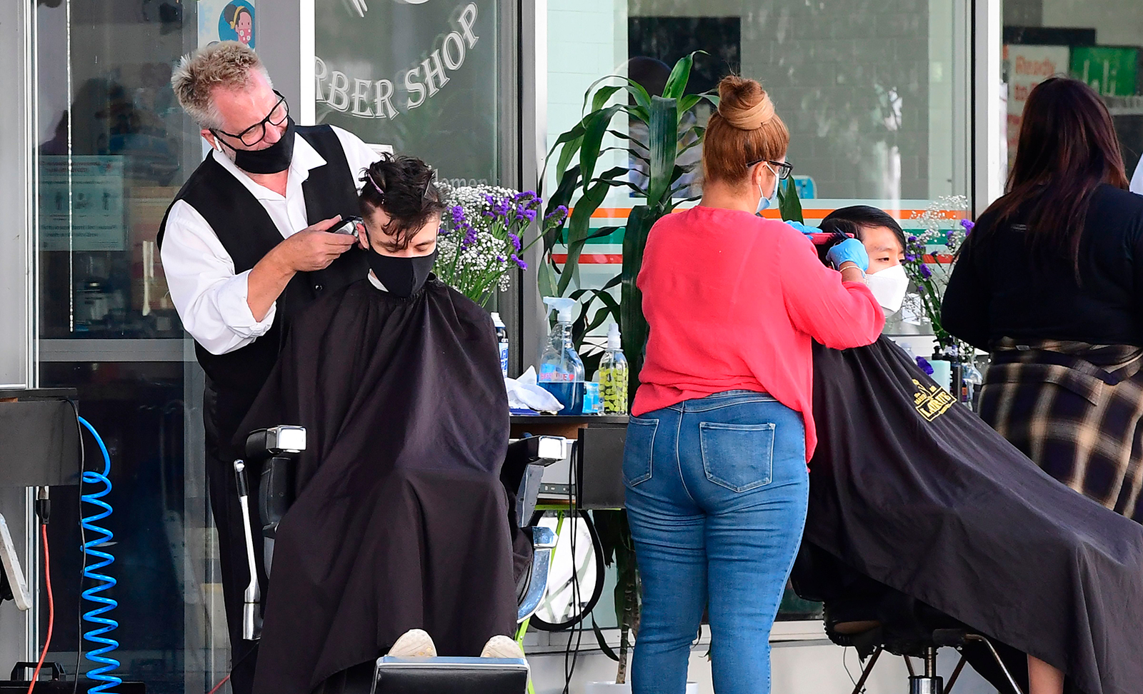 Hairdressers work on customers outdoors in Los Angeles on Friday, August 28.