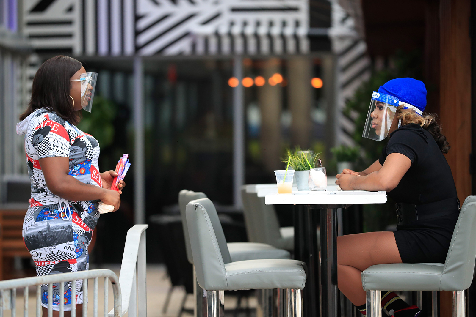 Two women wearing face masks speak at a table in The Palace restaurant on July 3, in Miami Beach, Florida.