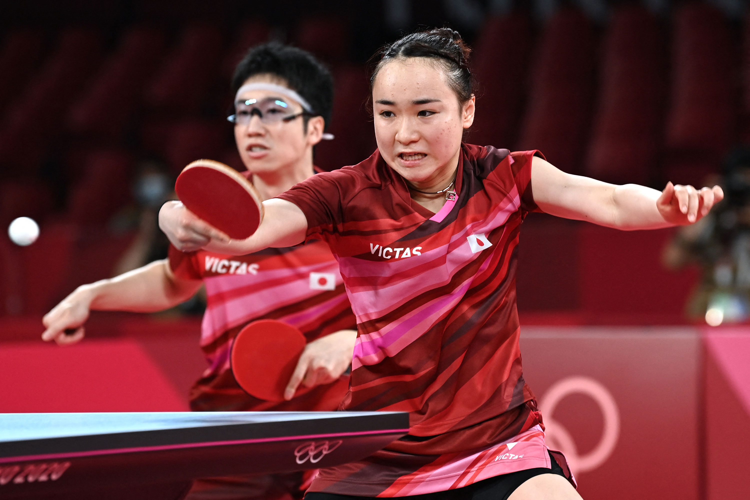 Japan's Jun Mizutani, left, and Mima Ito compete against China's Xu Xin and Liu Shiwen in their mixed doubles table tennis final match on July 26.