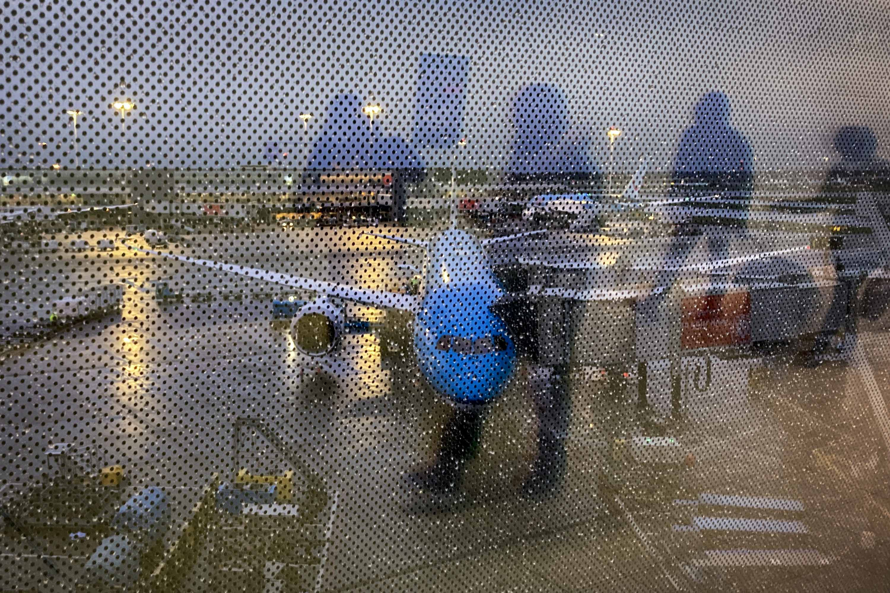 Arriving passengers are reflected in a screened window at the airport in Amsterdam, Netherlands, on December 24.
