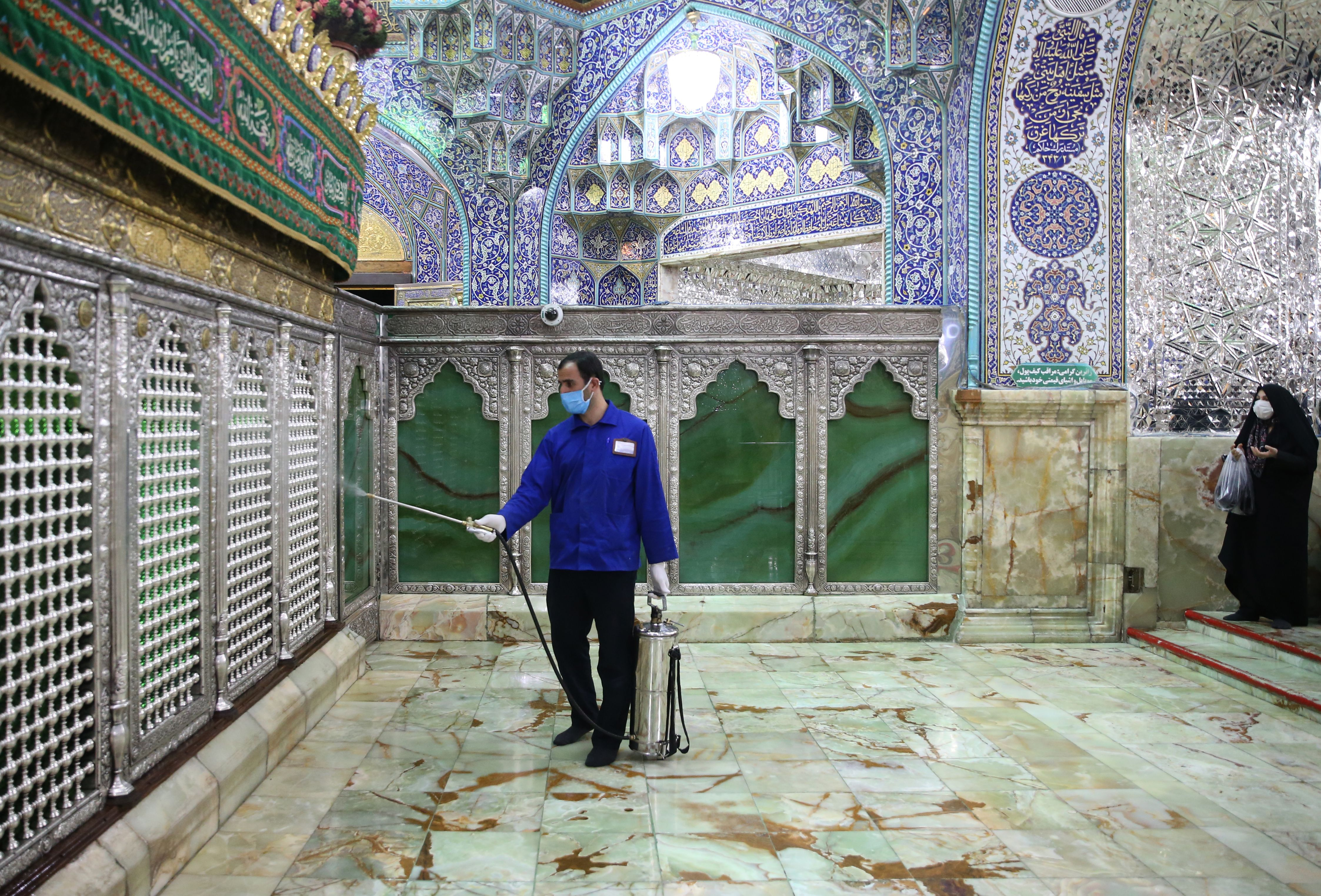 A worker disinfects Qom's Masumeh shrine on Tuesday. The city is the epicenter of Iran's virus outbreak.