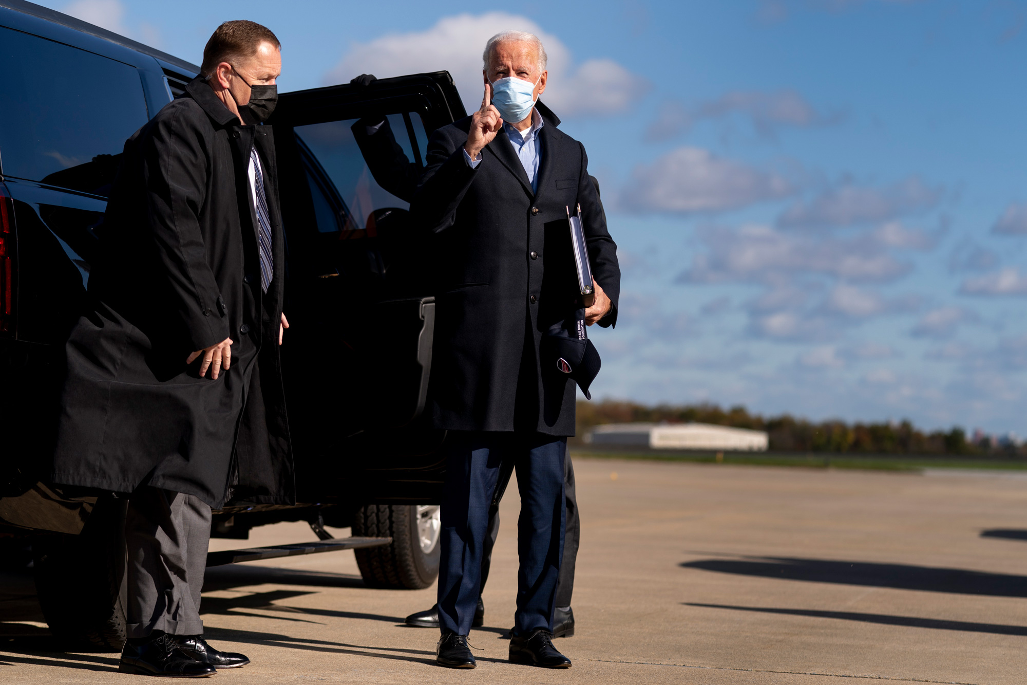 """Democratic presidential candidate Joe Biden holds up his finger and shouts """"One Day"""" to members of the media as he boards his campaign plane in Wilmington, Delaware, November 2."""