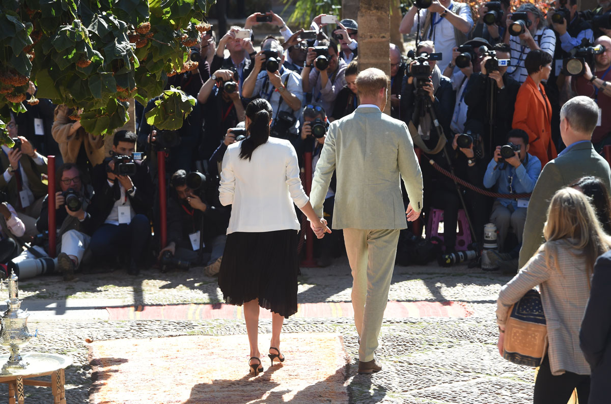 Prince Harry and Meghan, Duchess of Sussex, view the media as they walk through the Andalusian Gardens in Rabat, Morocco on February 25, 2019.