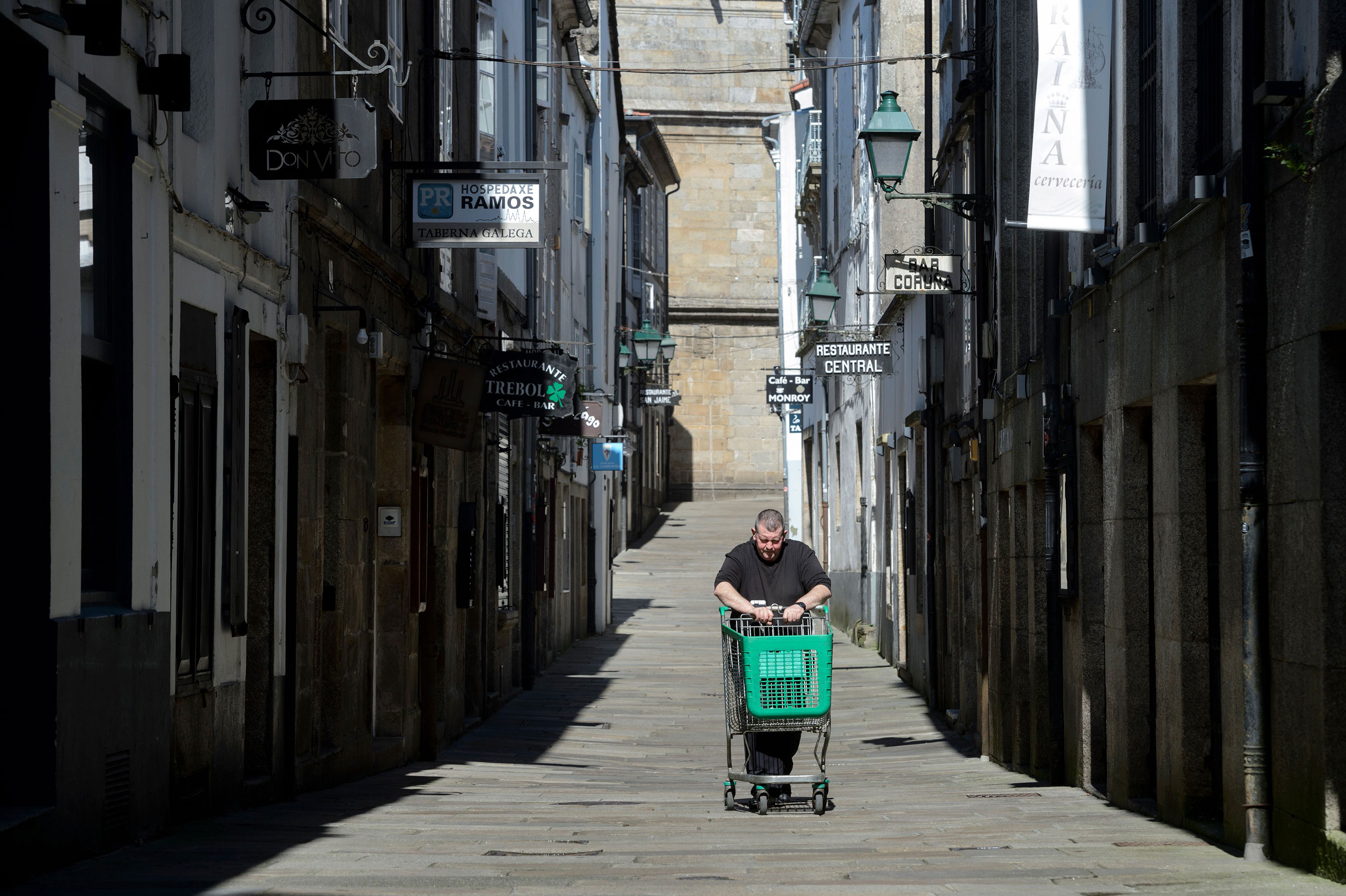 A man pushes an empty cart in Santiago de Compostela, on March 14, 2020 after regional authorities ordered all shops in the region be shuttered from today through March 26, save for those selling food, chemists and petrol stations, in order to slow the coronavirus spread. (Photo by MIGUEL RIOPA / AFP) (Photo by MIGUEL RIOPA/AFP via Getty Images)