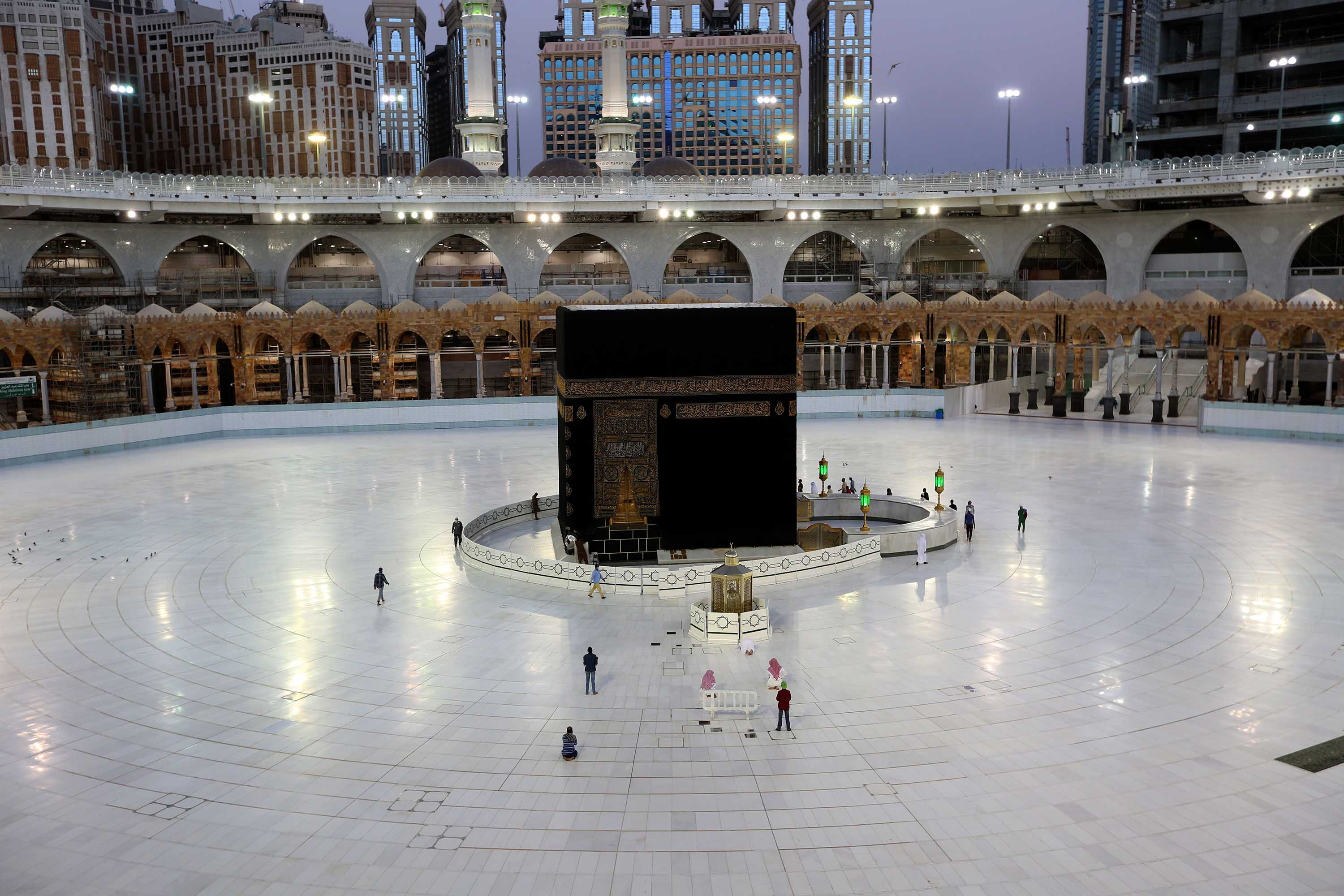 A handful of worshippers are seen praying at the Ka'aba, Islam's holiest shrine, at the Grand Mosque complex in Mecca, Saudi Arabia, on June 23.
