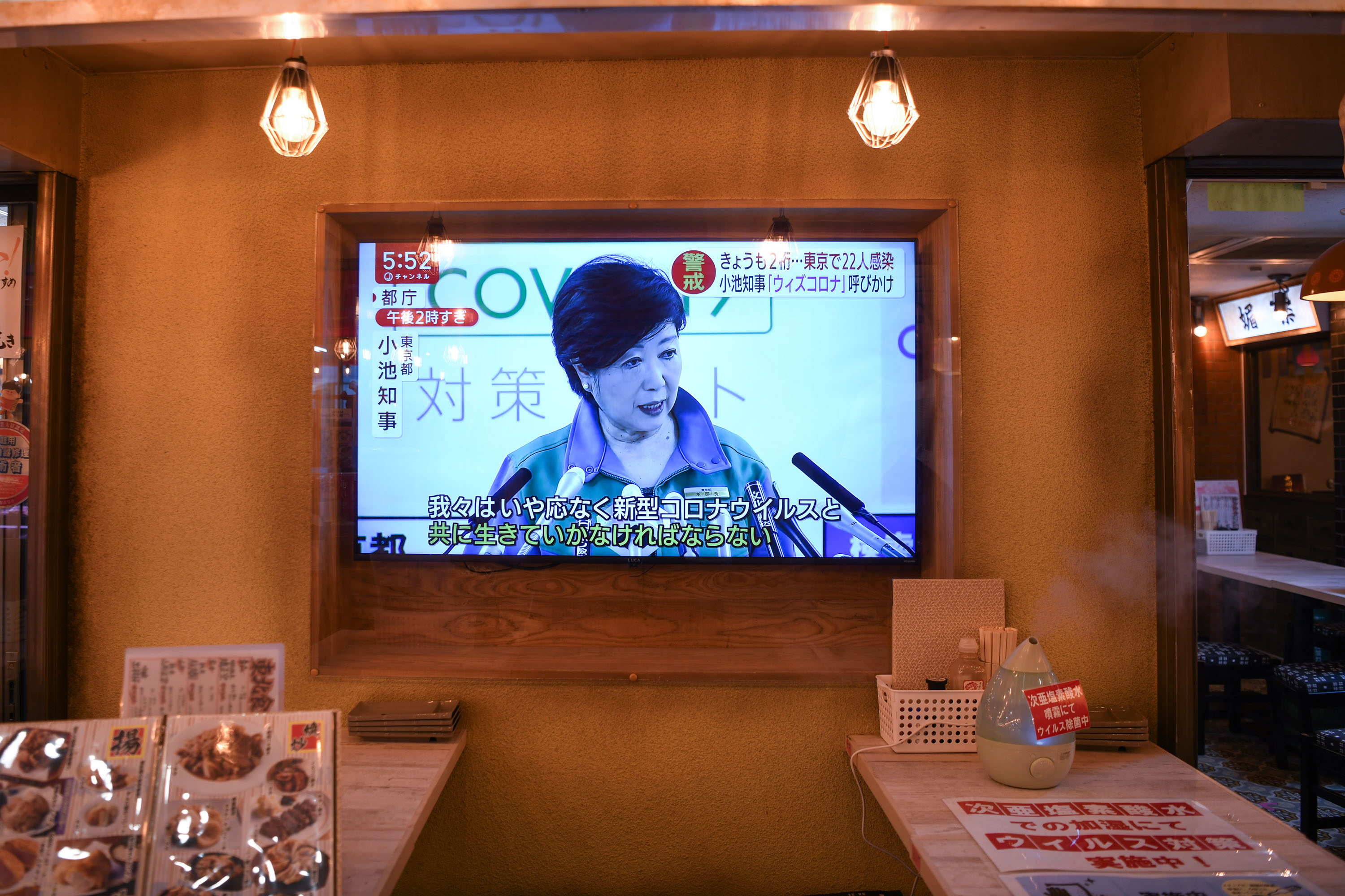 A television screen in a Tokyo hotel displays a news conference held by Gov. Yuriko Koike on Friday, May 29.