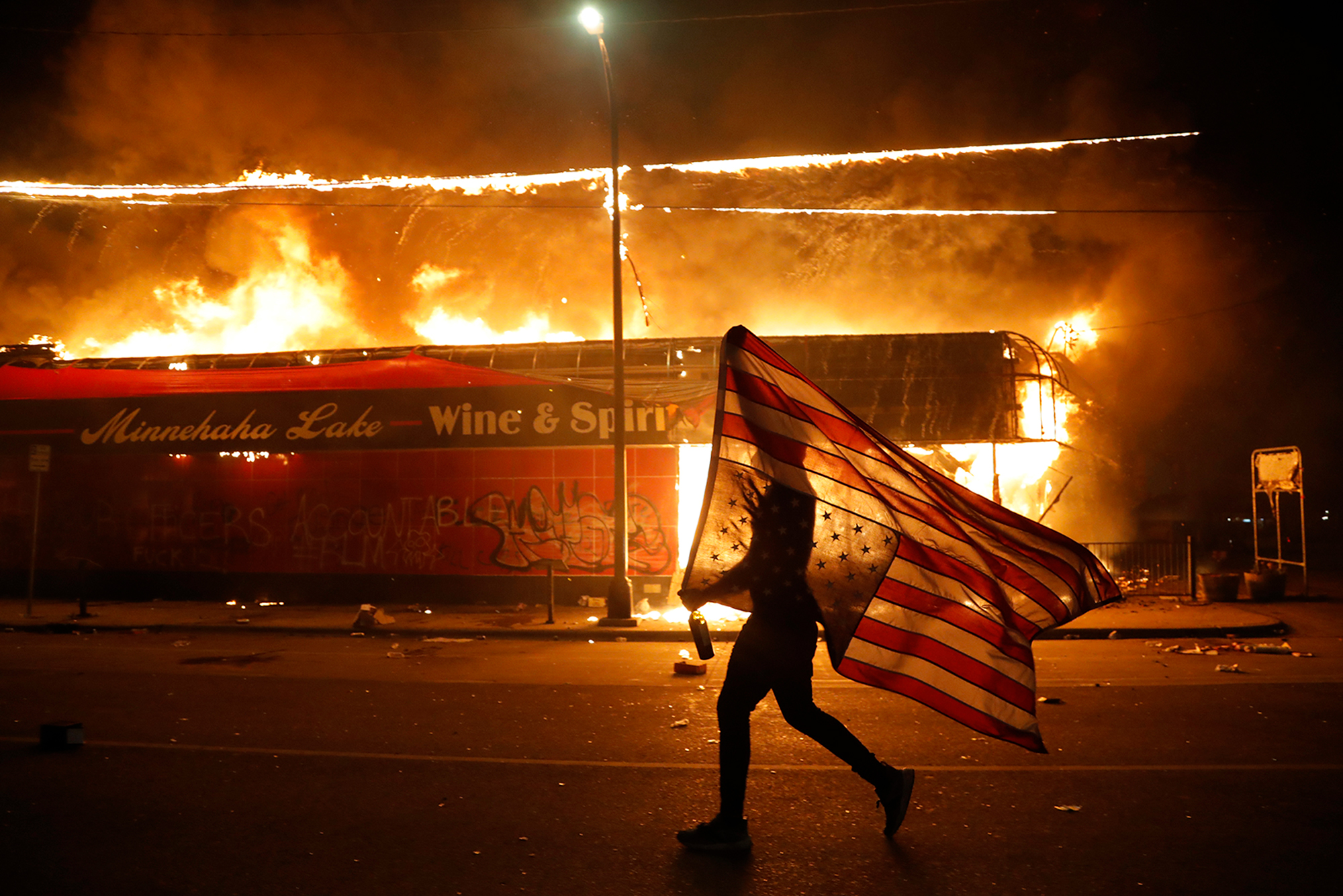 A protester carries the carries a U.S. flag upside-down, a sign of distress, next to a burning building on May 28, in Minneapolis.