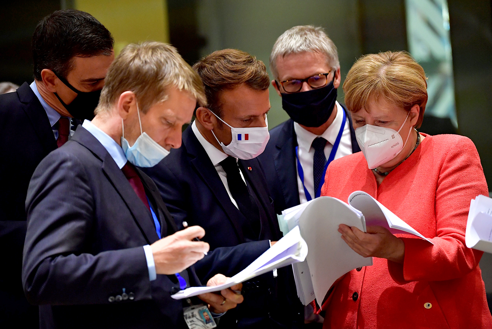 Spain's Prime Minister Pedro Sanchez (left), French President Emmanuel Macron (center) and German Chancellor Angela Merkel (right) look into documents during an EU summit in Brussels, Belgium on July 20.