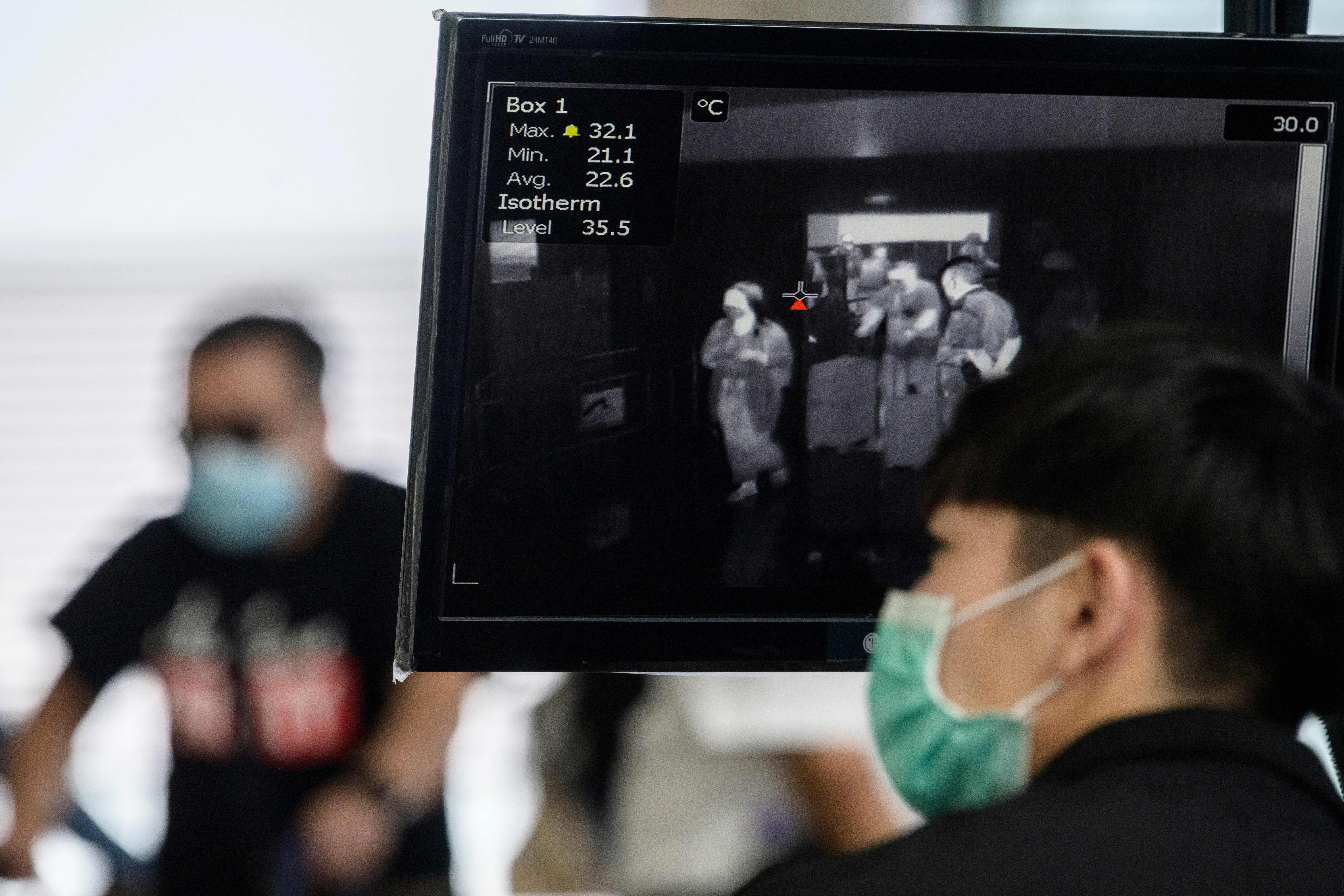 A worker at the Hong Kong International Airport monitors a thermal screening display as passengers arrive on March 10.