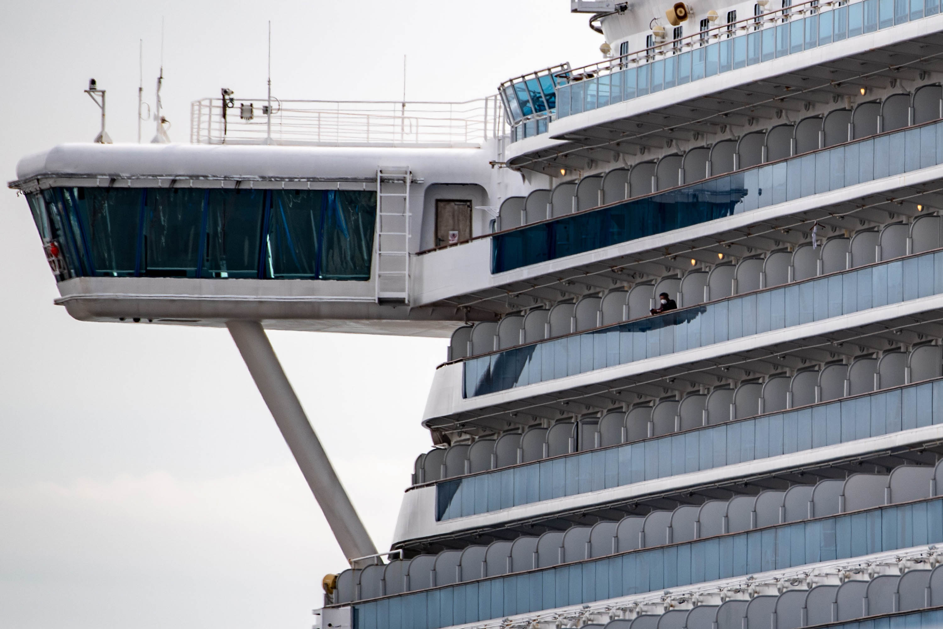 A passenger wearing a face mask looks out from a cabin of the Diamond Princess cruise ship quarantined at Daikoku pier cruise terminal in Yokohama on Thursday.