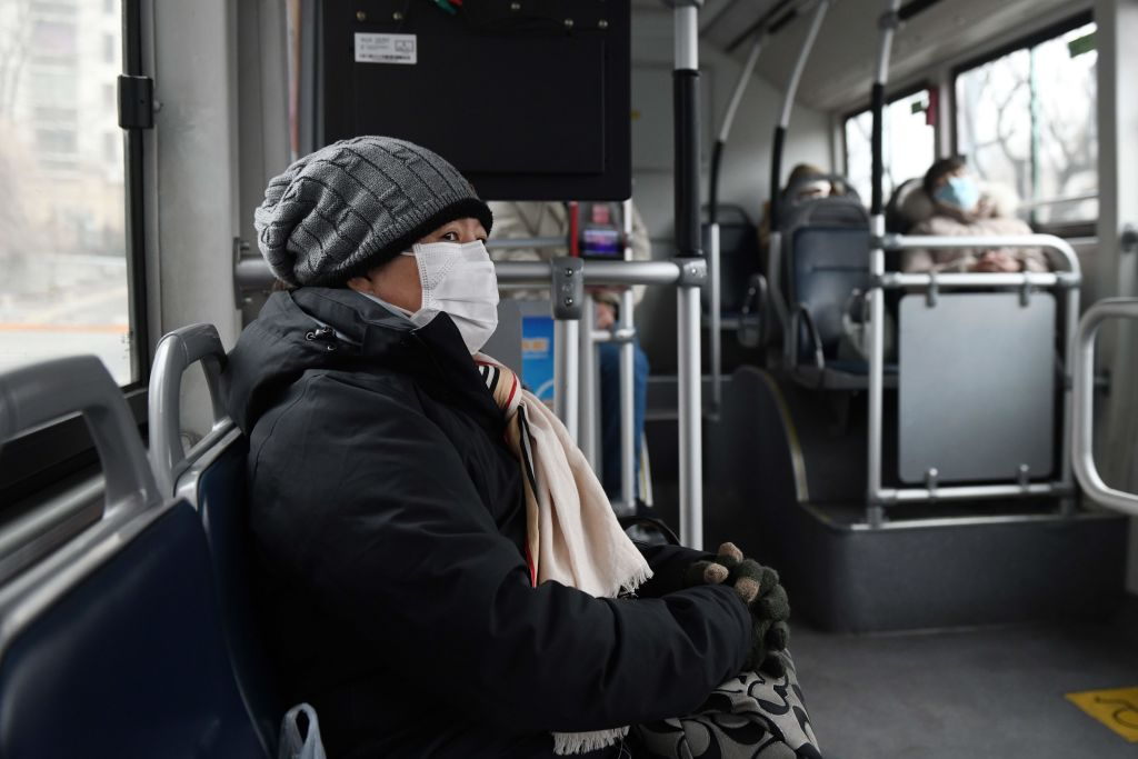 A woman wears a wear face mask as she rides on a bus in Beijing on February 13.