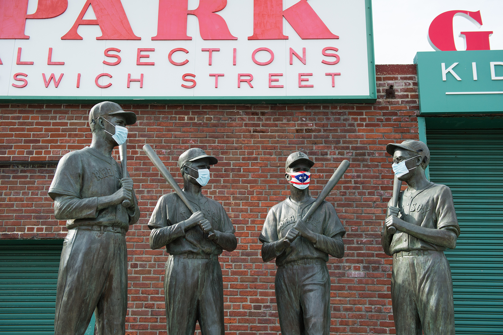 A mask is placed on the Teammates Statue on Ispwich Street on Opening Day at Fenway Park on July 24 in Boston.