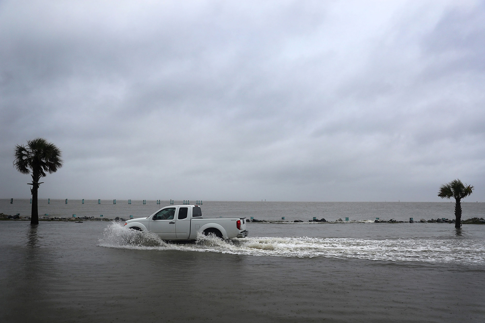 A driver navigates along a flooded road as the outer bands of Hurricane Sally come ashore on Tuesday in Bayou La Batre, Alabama.