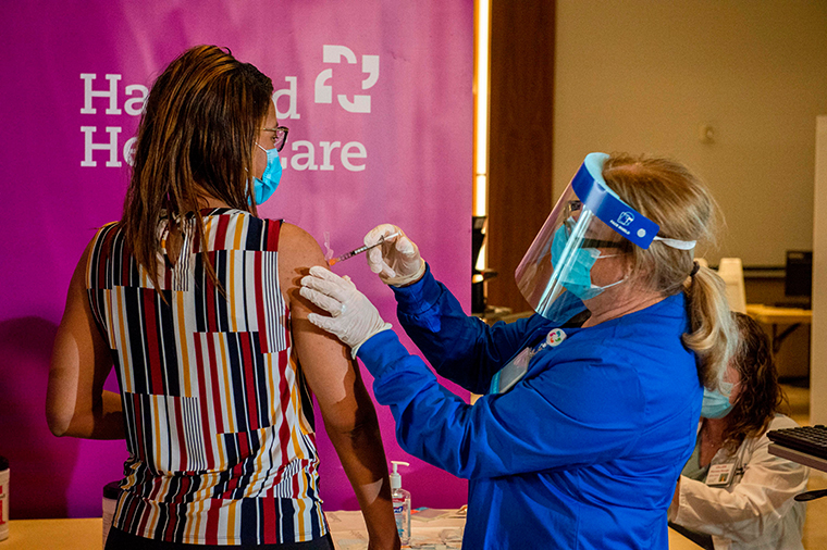 Dr. Melisha Cumberland is given the the second dose of the Pfizer/BioNTech vaccine twenty-one days after receiving the first shot from RN Valerie Massaro of Hartford HealthCare, at the Hartford Convention Center in Hartford, Connecticut on January 4, 2021.