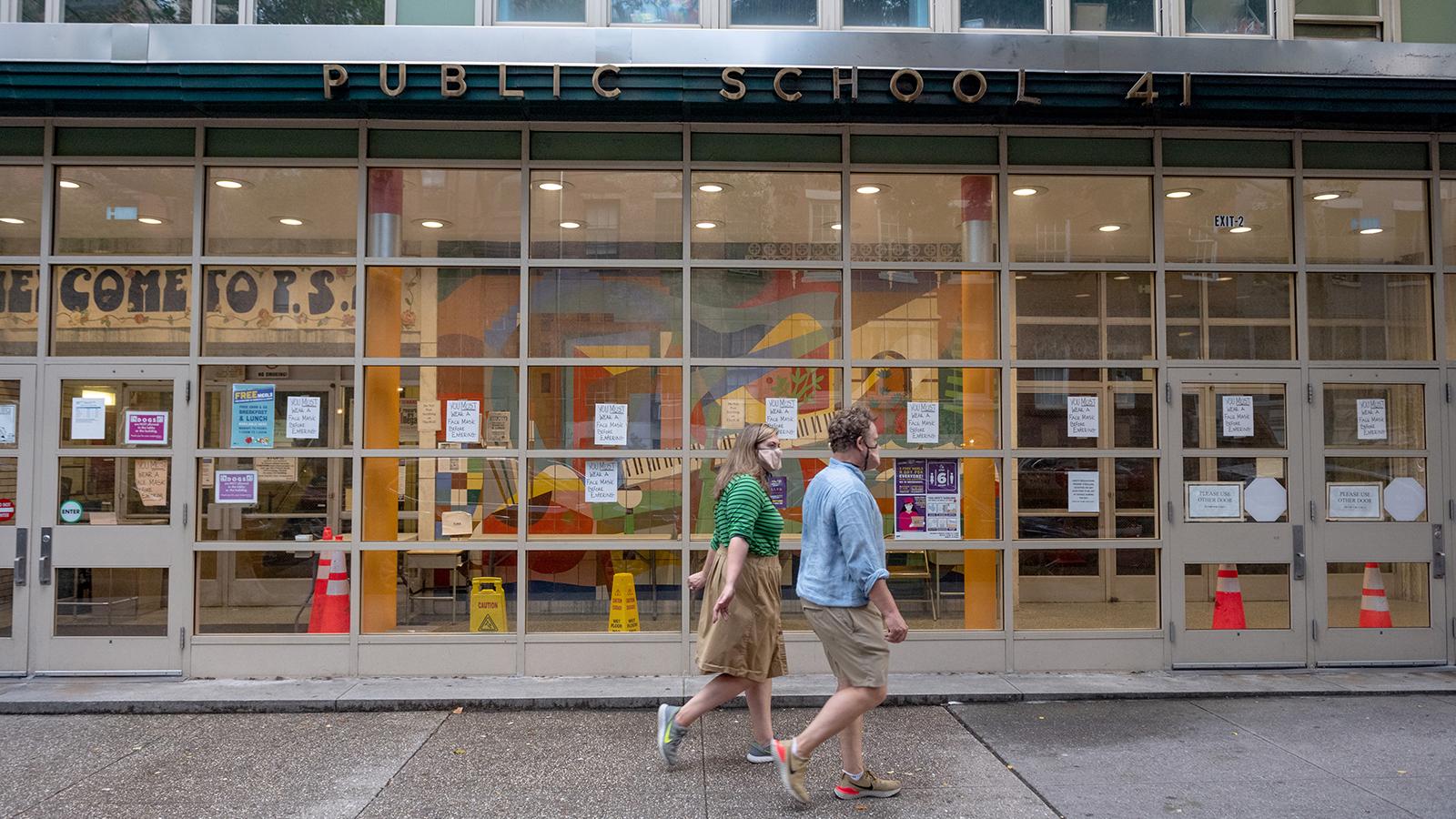 People wearing masks walk past a public school in the Greenwich Village on July 8 in New York.