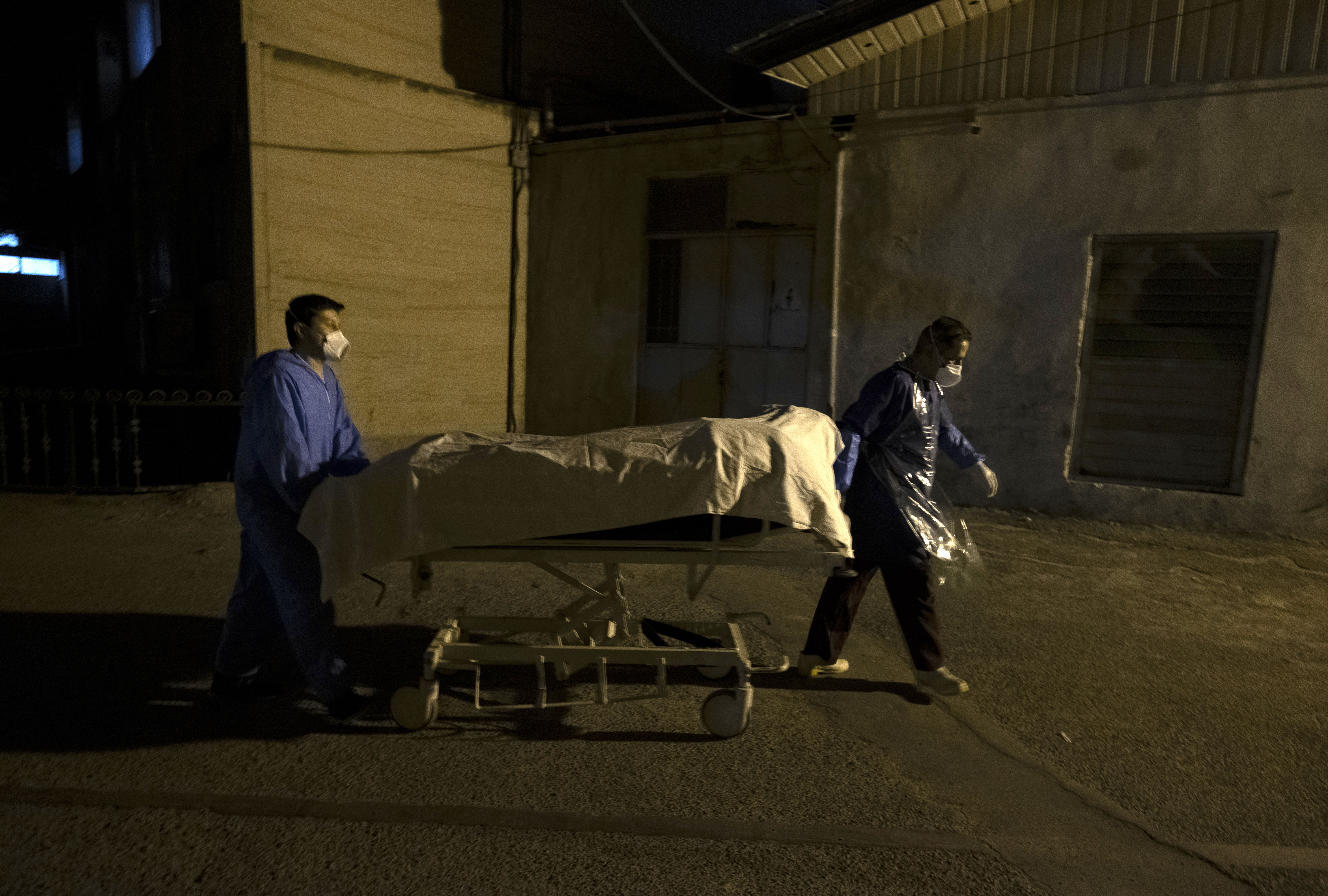 Hospital personnel take the bodies of two people said to have died from Covid-19 to a morgue in the Shahr-e Rey neighborhood in southern Tehran, Iran, on June 20.