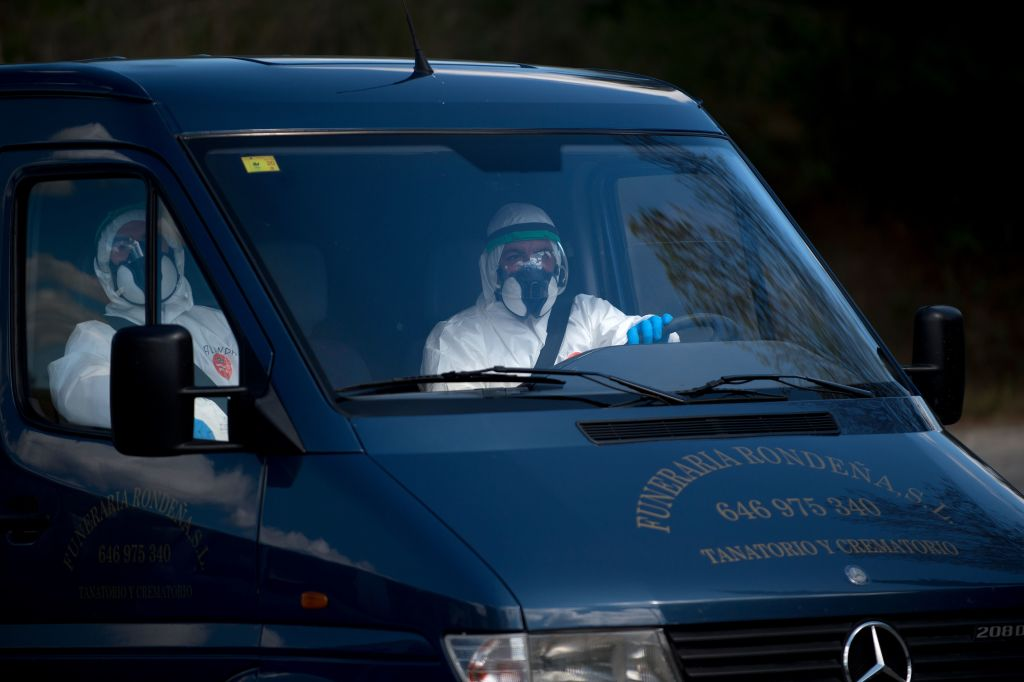 Mortuary workers in full protective gear ride in a hearse in Ronda on April 3, amid a national lockdown to prevent the spread of the coronavirus.