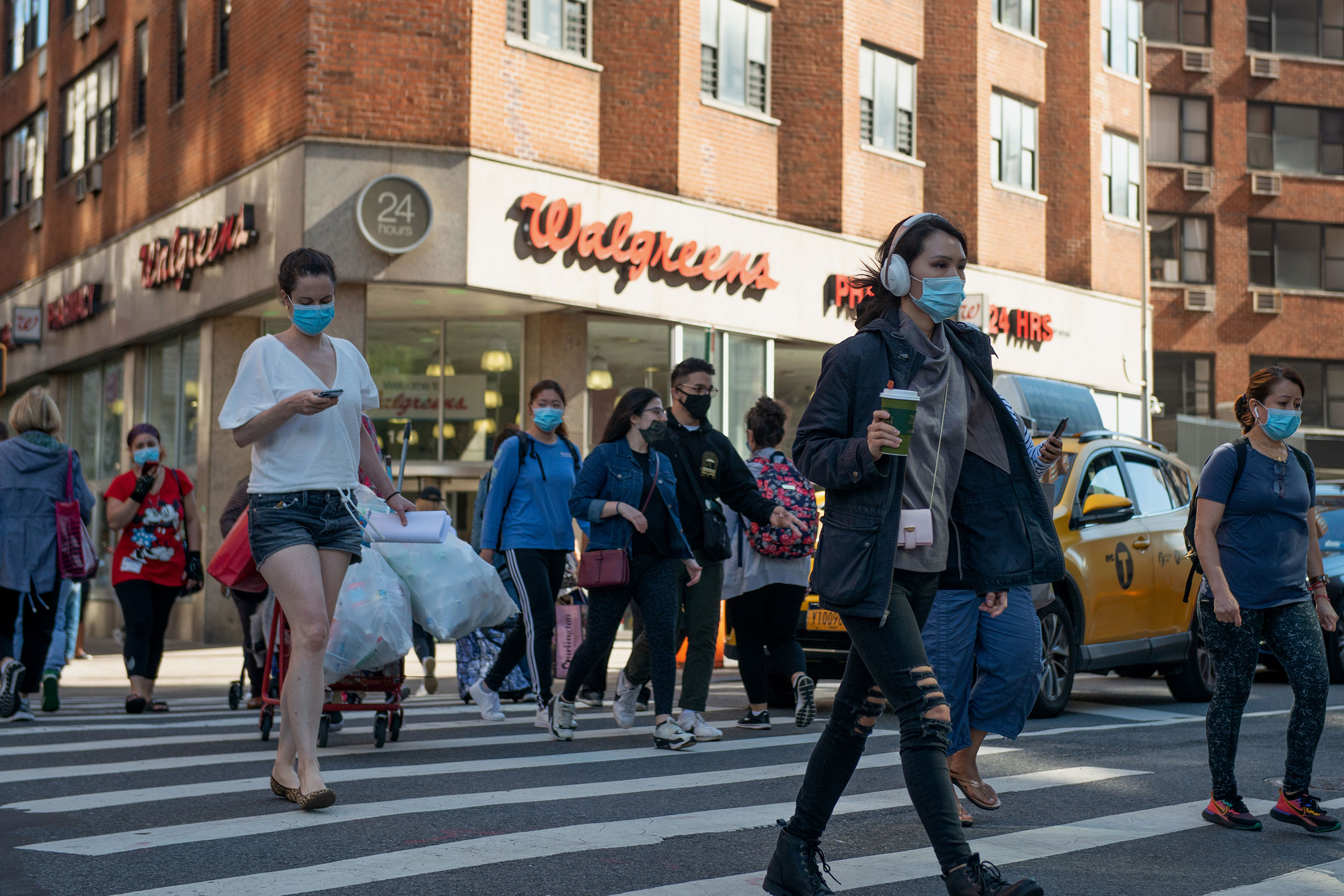 People cross the street near a Walgreens store on September 30 in New York City.