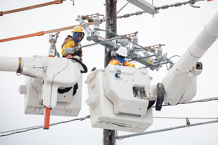 Workers repair a power line in Austin, Texas, on Wednesday, February 18.
