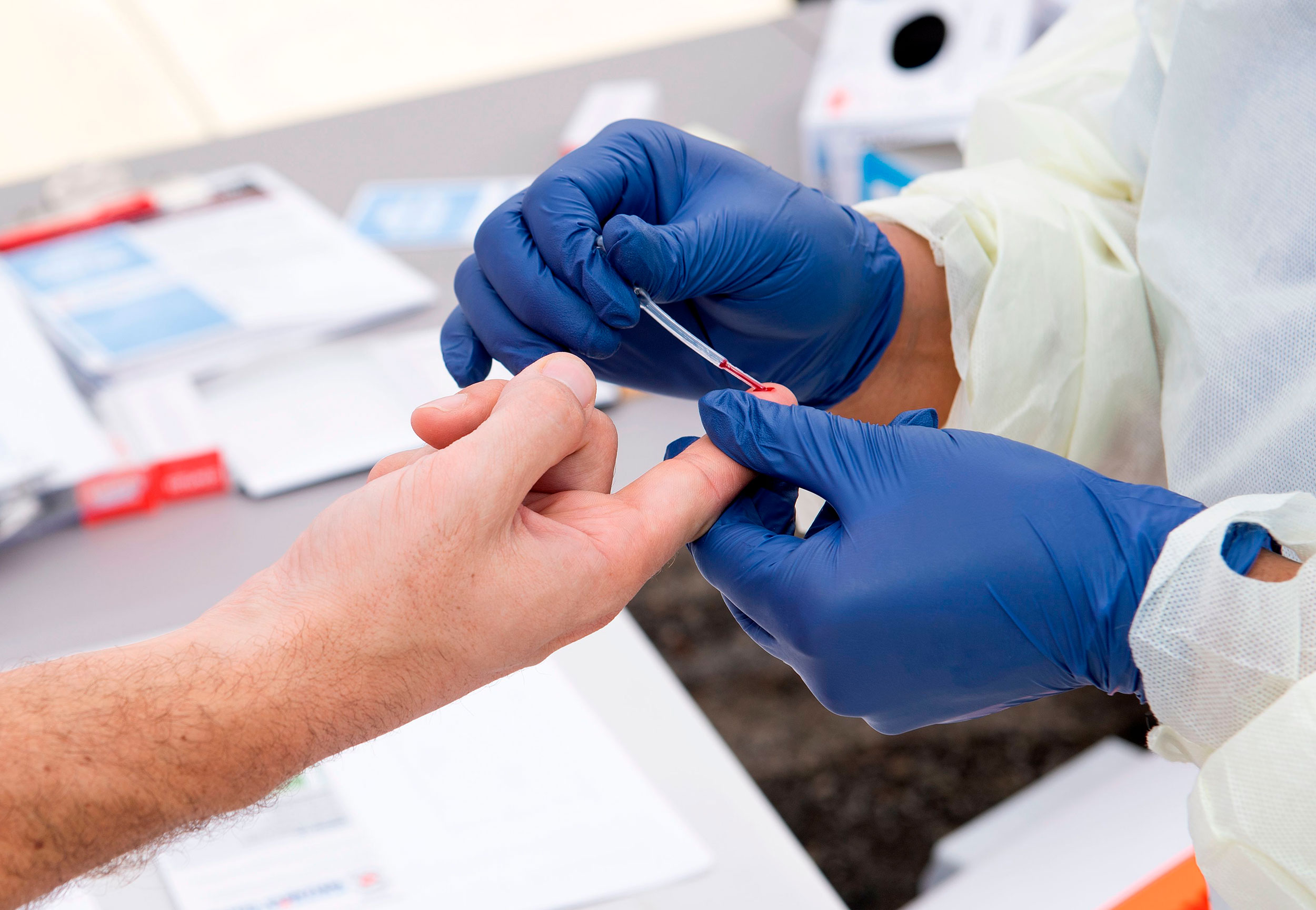 A health worker takes a drop of blood for a Covid-19 antibody test at the Diagnostic and Wellness Center in Torrance, California, on May 5, 2020.