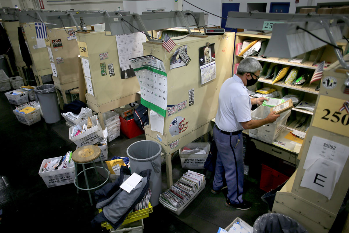 A letter carrier sorts mail at his station inside the Roxbury Post Office in Boston, MA on December 1.