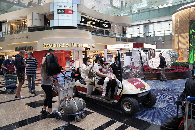 Travelers ride on a cart as they pass through a transit area at Singapore Changi Airport in Singapore, on Tuesday, March 17.
