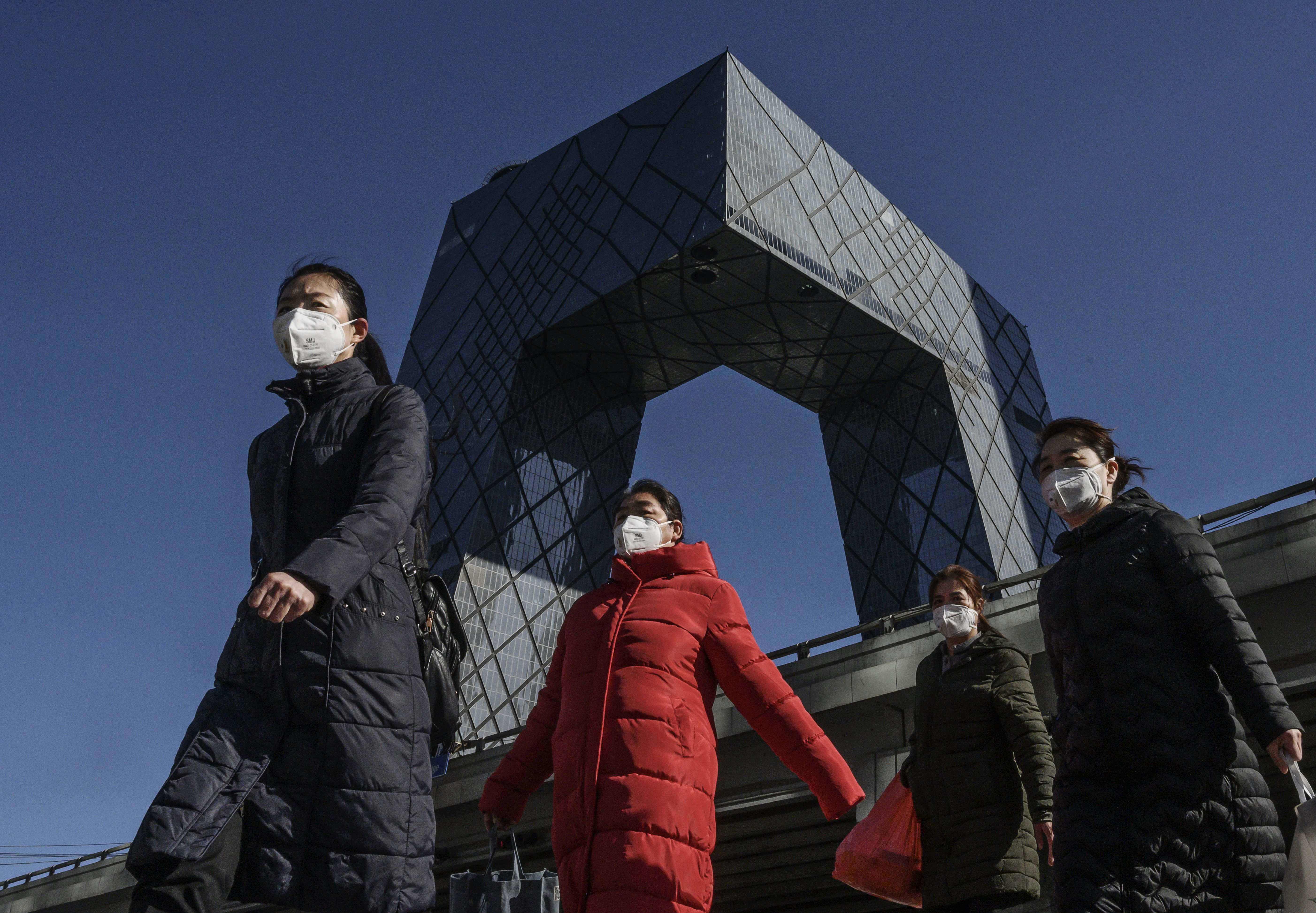 Chinese women wear protective masks on their way to work in Beijing.