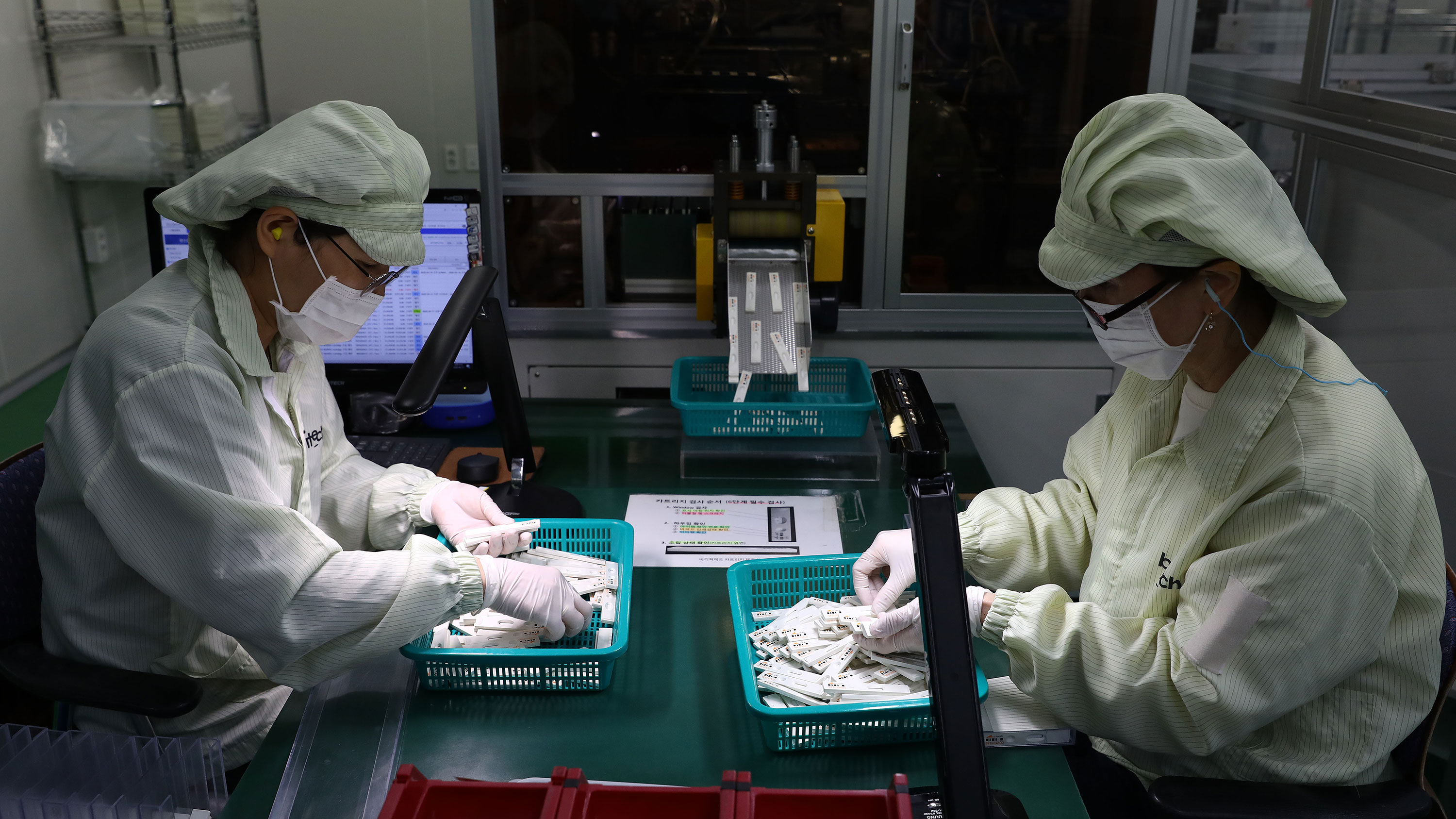 Employees work on the production line of testing kits used in diagnosing the coronavirus at the Boditech Med Inc. headquarters in Chuncheon, South Korea on April 17.