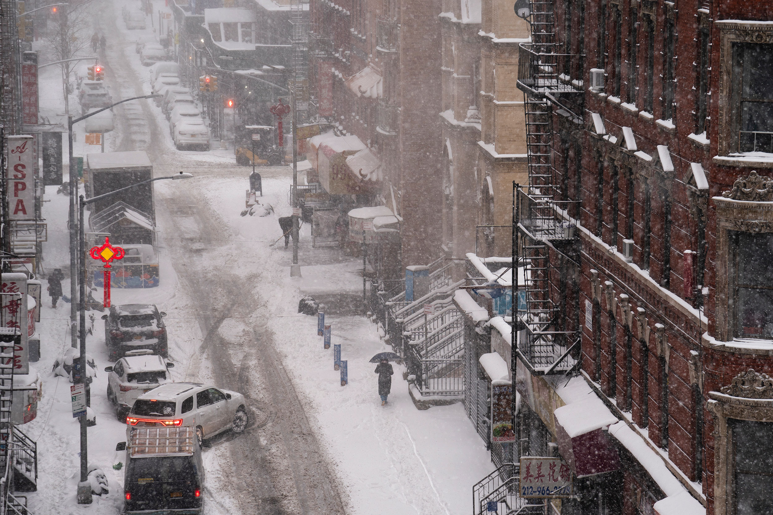 A pedestrian walks down a snow-covered sidewalk in New York on Monday.