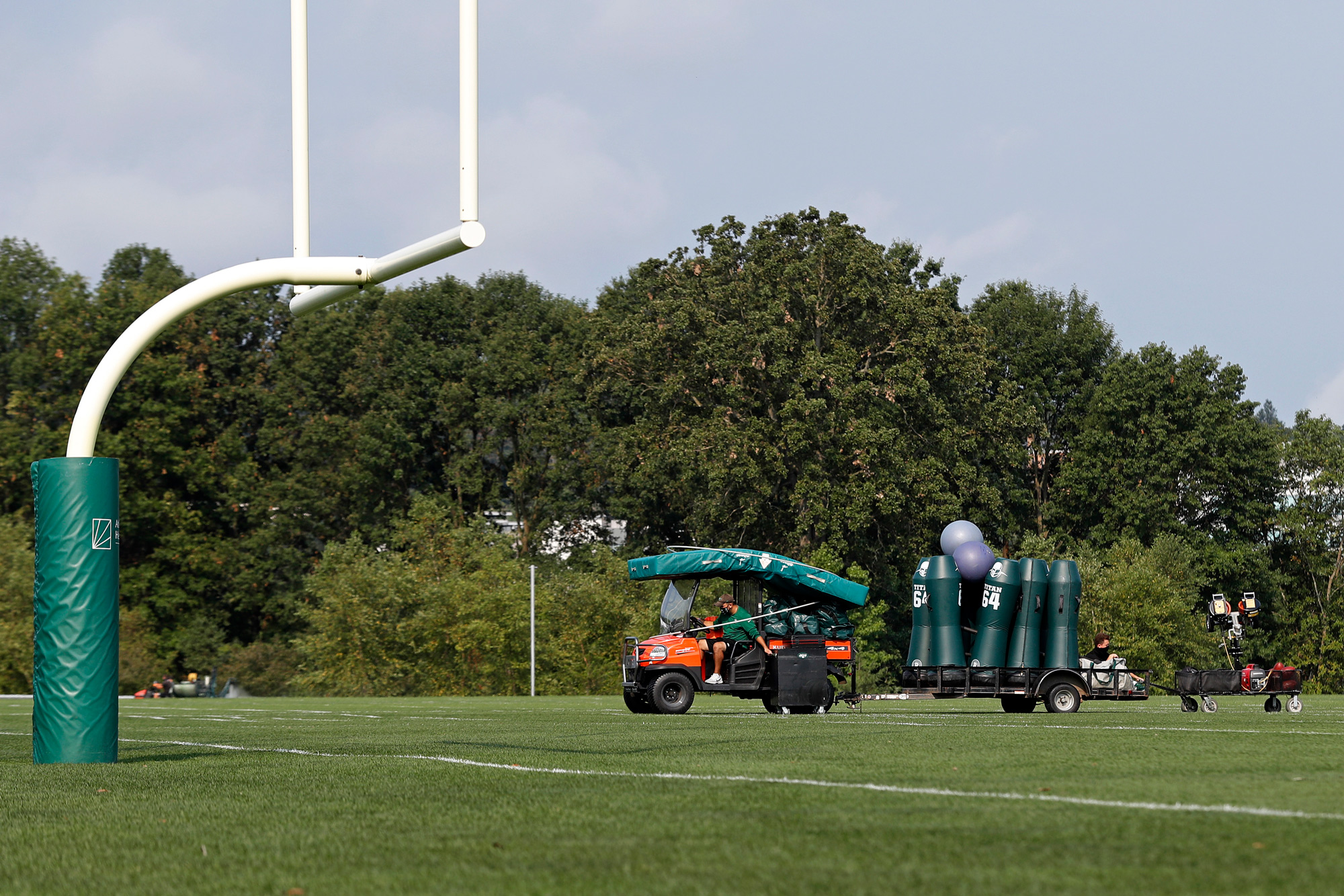 New York Jets personnel clear practice equipment after practice was canceled at the NFL football team's training camp in Florham Park, New Jersey, on August 27.