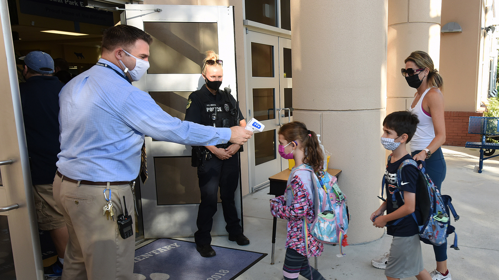 Principal Nathan Hay performs temperature checks on students as they arrive on the first day of classes for the 2021-22 school year at Baldwin Park Elementary School in Orlando, Florida.