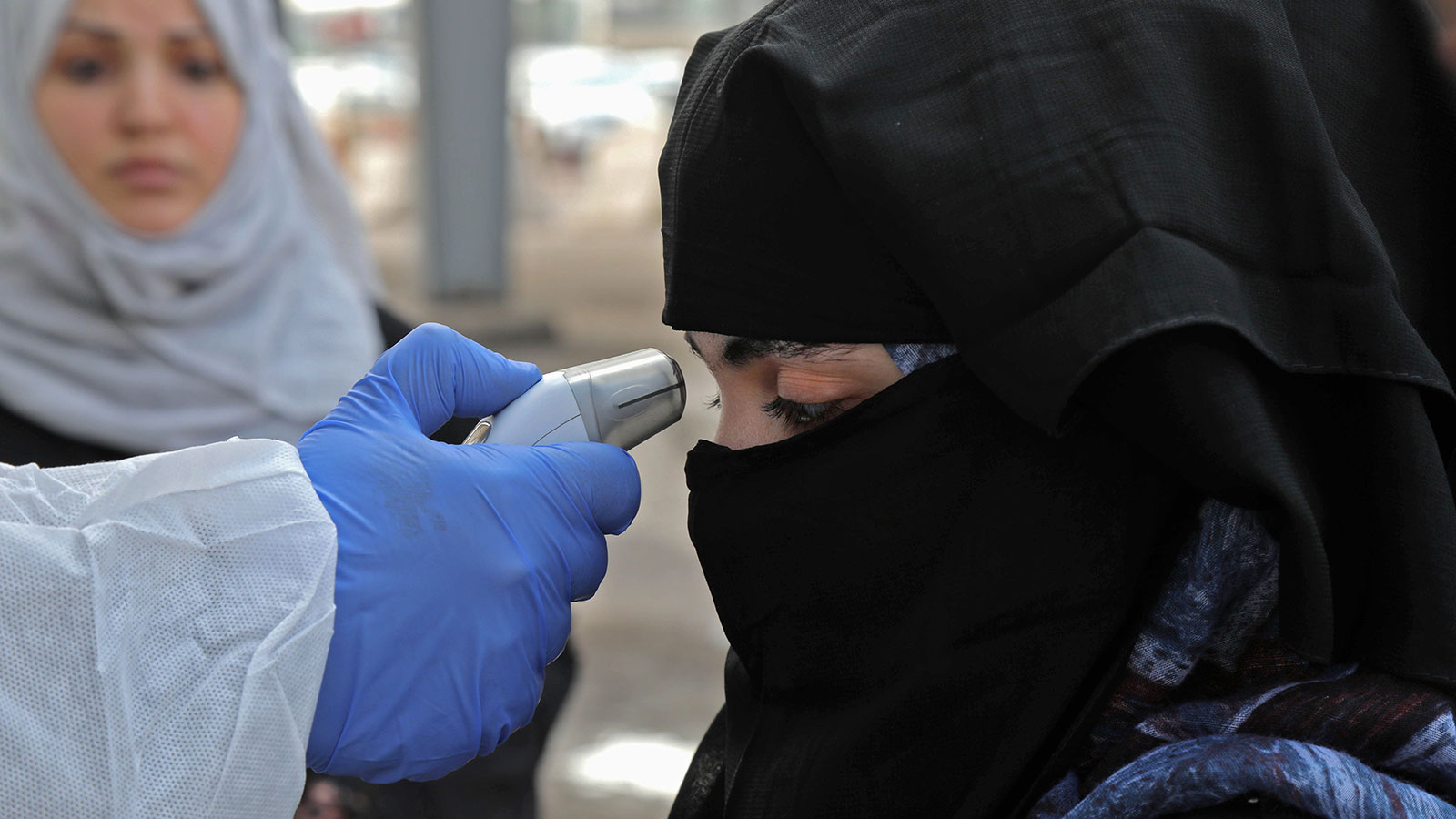 A medic checks the body temperature of a woman arriving to the checkpoint of Arbil, the capital of the northern Iraqi Kurdish autonomous region, on March 2.
