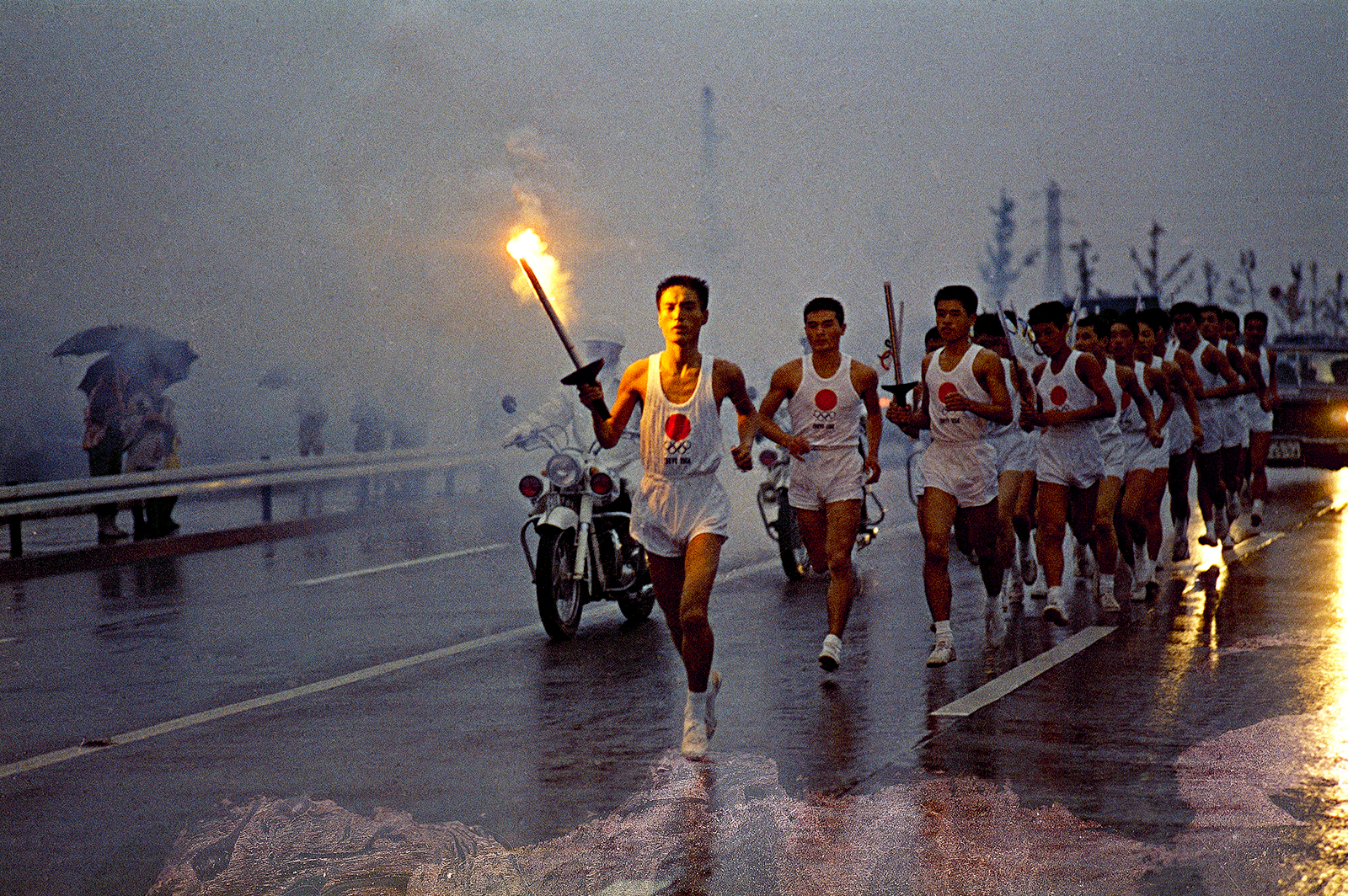 Torchbearers run through the rain on their way to the National Stadium in Tokyo in October 1964.