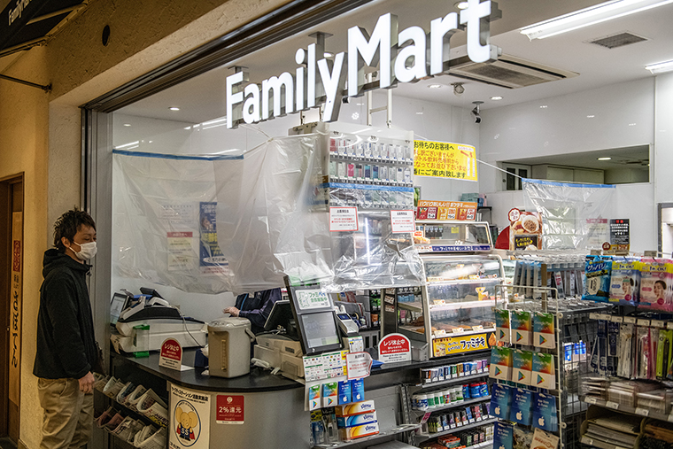 A convenience store employee serves a customer from behind plastic sheeting that has been put up to protect staff from customers who may have coronavirus, on April 14, in Tokyo.