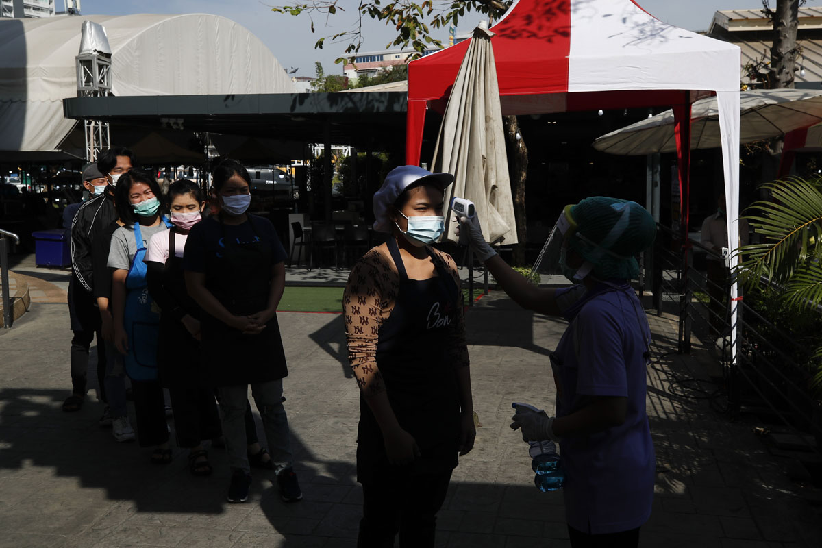 Migrant workers have their temperature checked before being screened by members of the Health Department at a food market in Bangkok, Thailand on December 22.