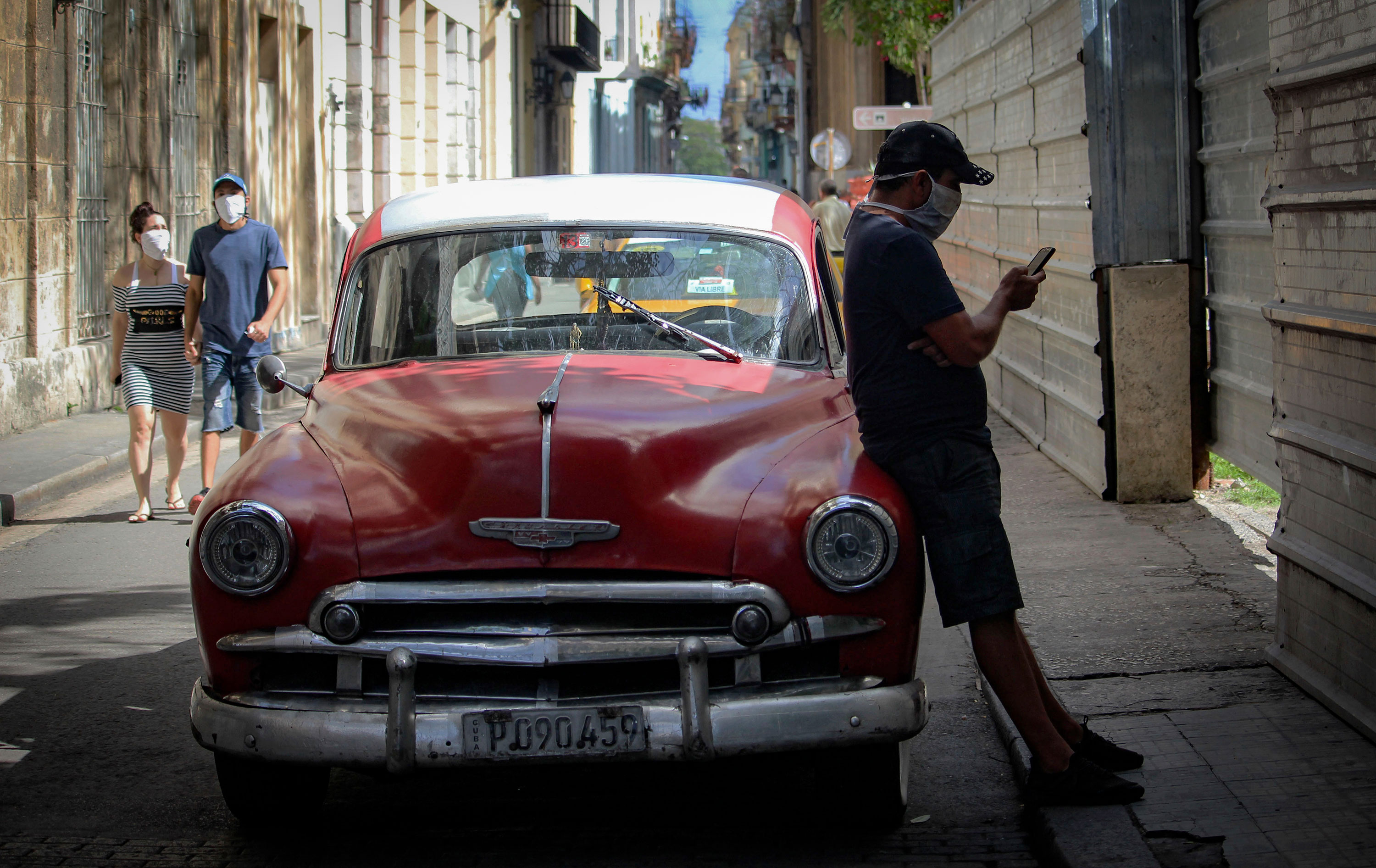 A man wearing a face mask looks at his mobile phone while a couple walks by in Havana, Cuba, on May 18.