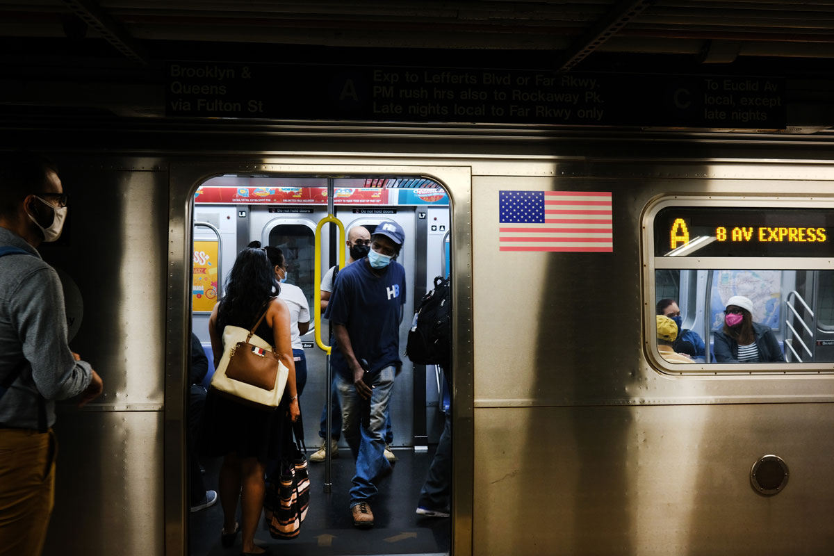 People wearing face masks take the subway on September 10 in New York City.