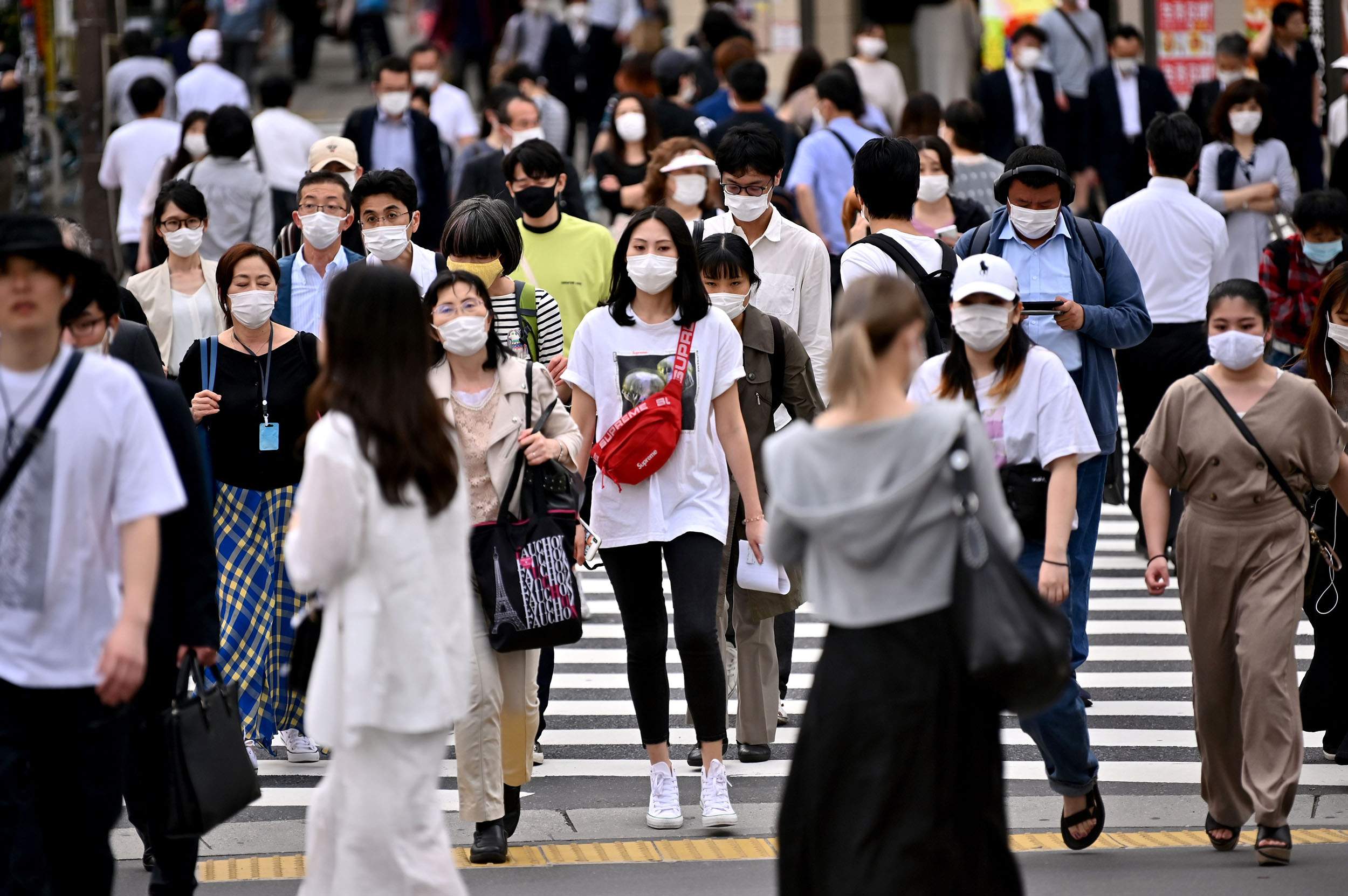 People wearing face masks cross a street on May 25, in Tokyo, Japan.