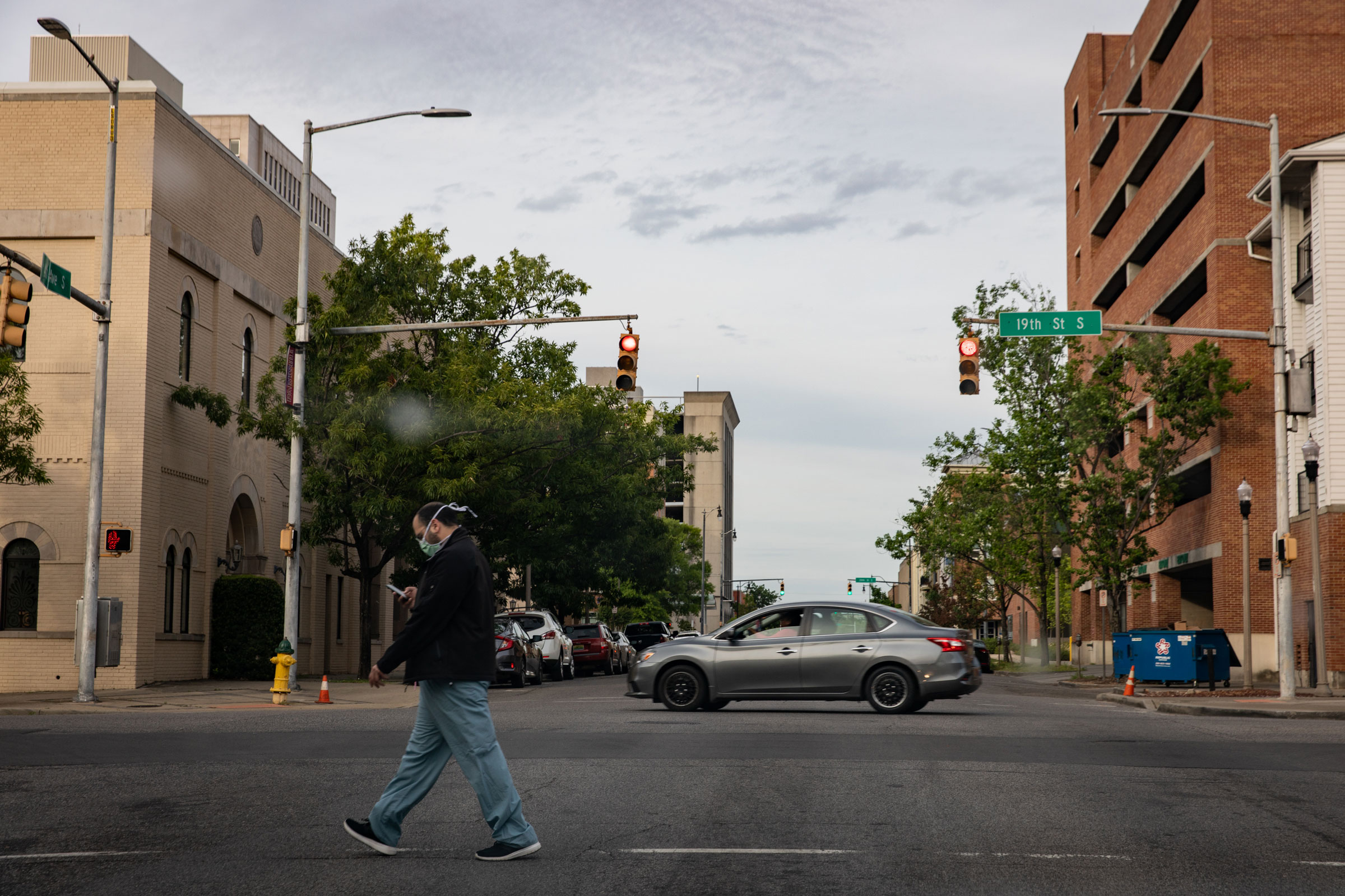 A pedestrian wearing scrubs and a mask crosses a street in Birmingham, Alabama, on April 28.